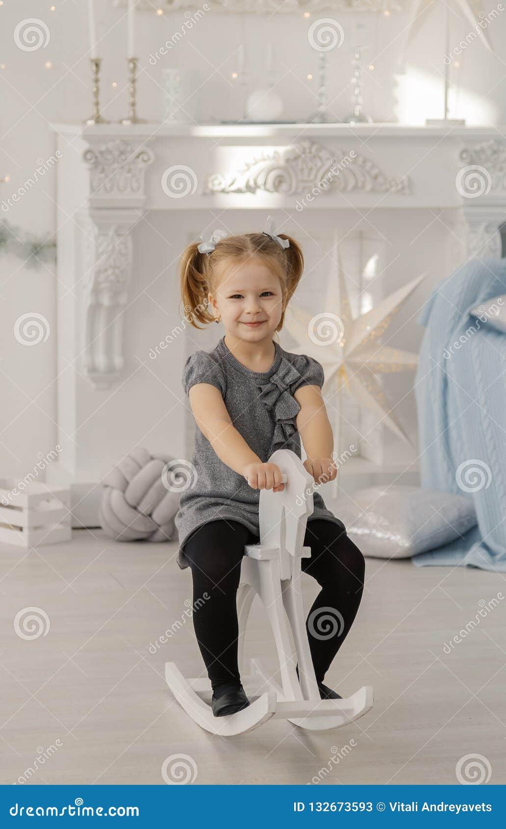 Piękna mała dziewczynka w białej sukni jak princess siedzi na zabawkarskim drewnianym koniu w rocznika studiu, nowy rok