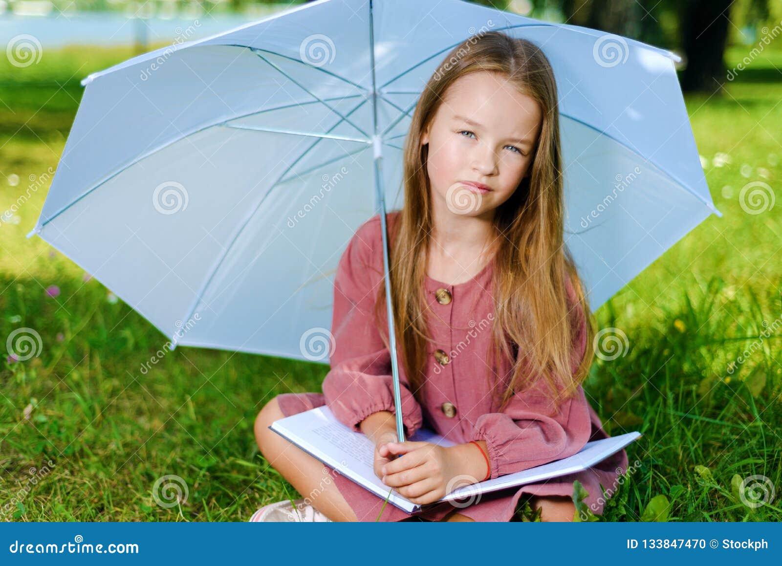 Piękna mała dziewczynka w menchii sukni siedzi w parku na trawie w jaskrawym słonecznym dniu