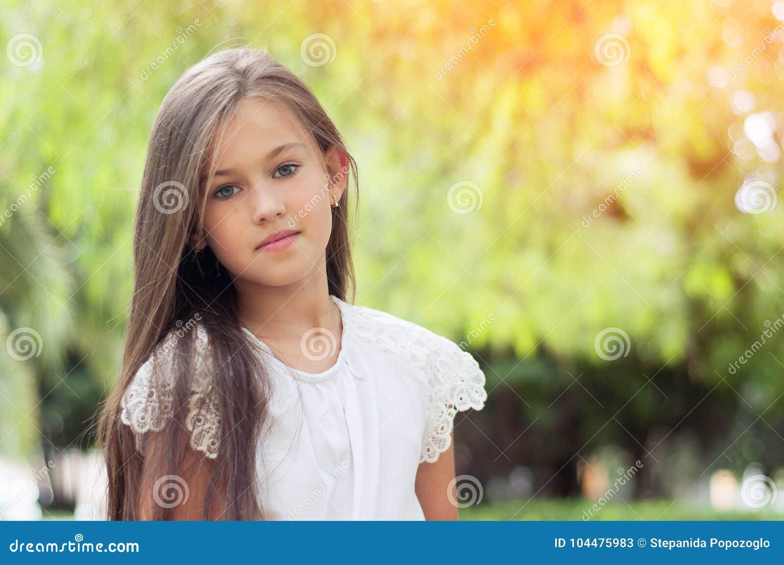 Piękna mała dziewczynka w parku z długie włosy i swee, i