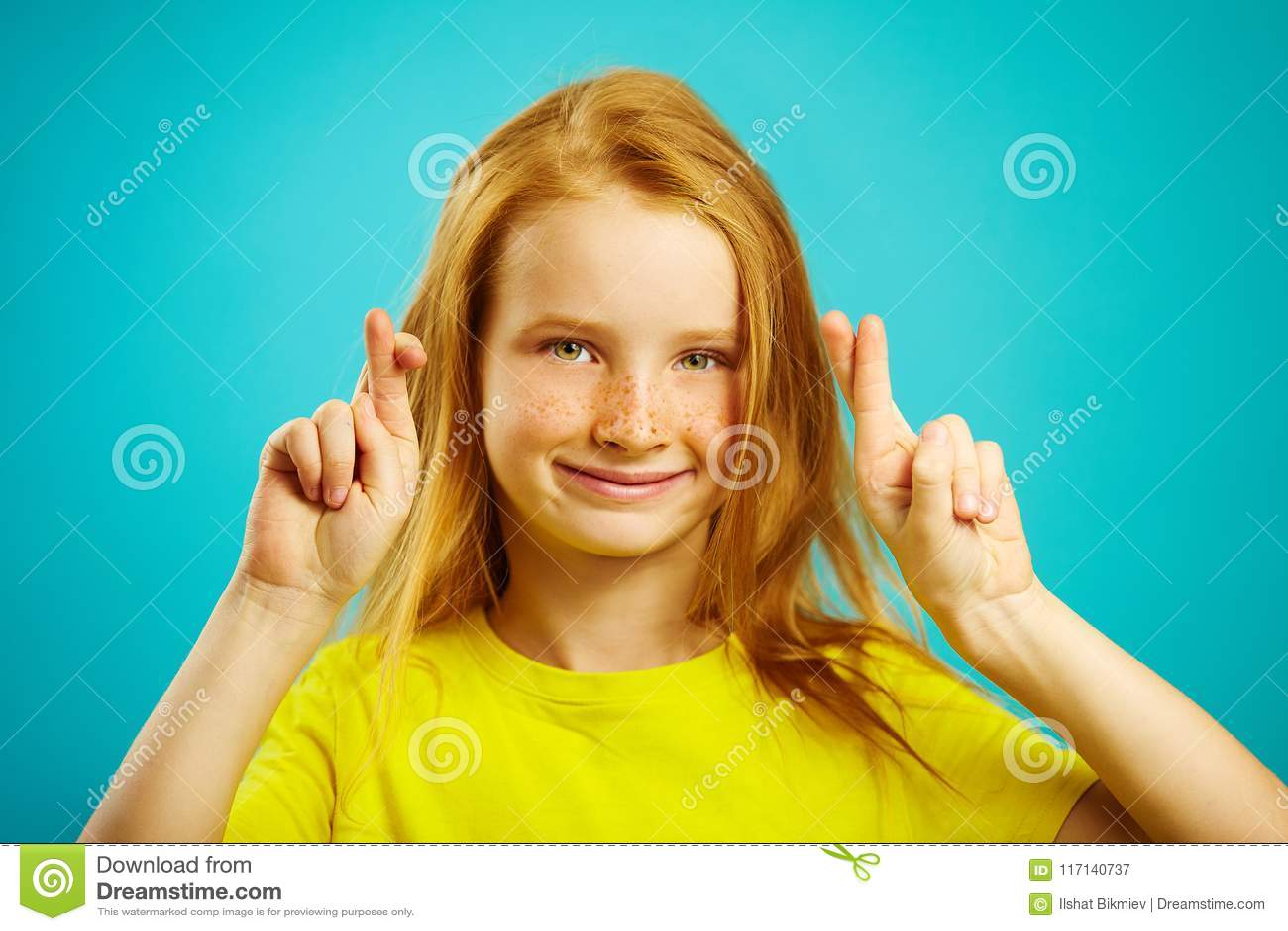 Piękna mała dziewczynka z czerwonym włosy i piegami robi życzeniu, palce krzyżujący, wiary w zadości sen, a