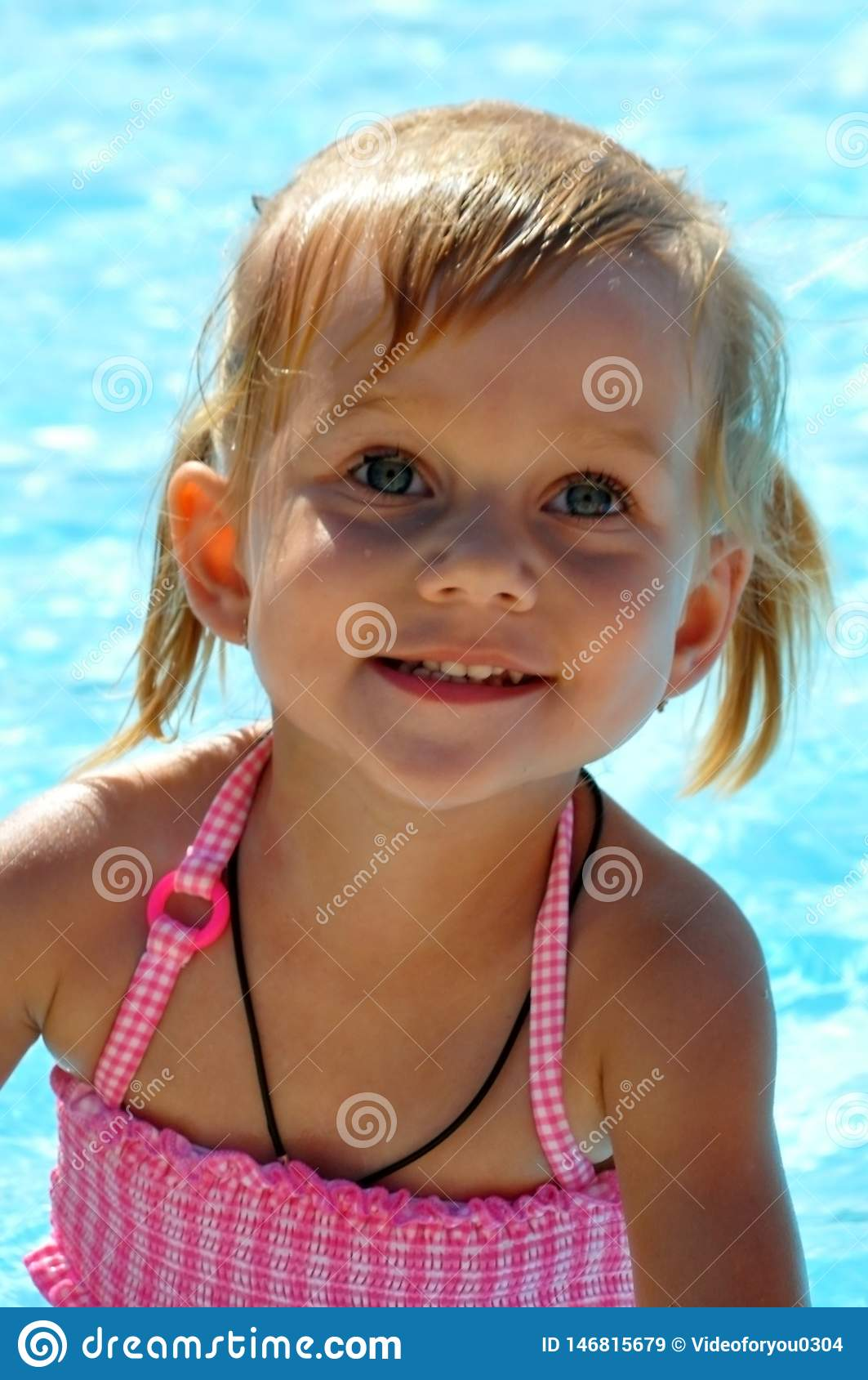 Piękna mała dziewczynka z niebieskimi oczami przeciw tłu basen