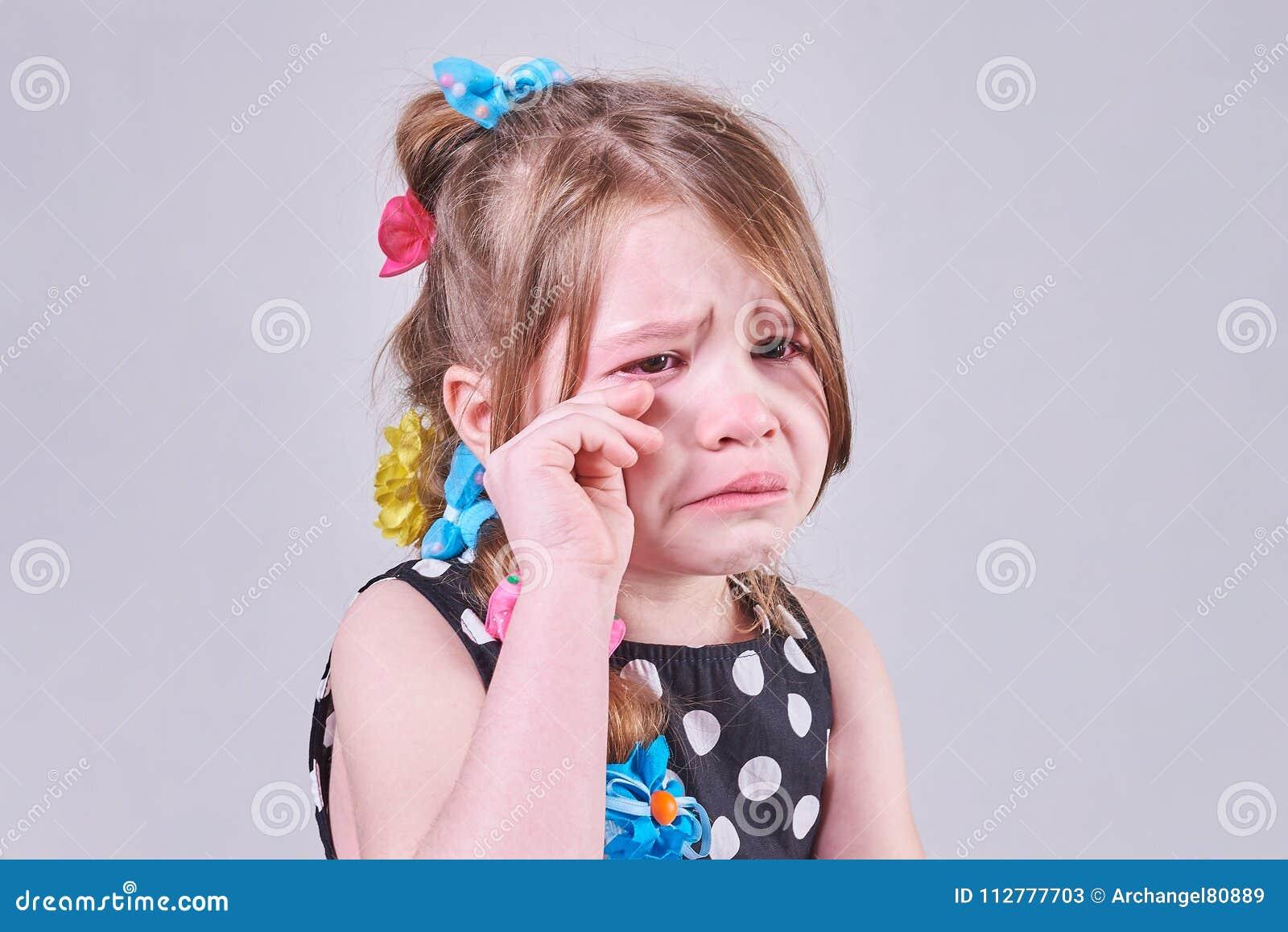 Piękna mała dziewczynka z smutnym wyrażeniem, płacze ona i wyciera łzy z jej rękami