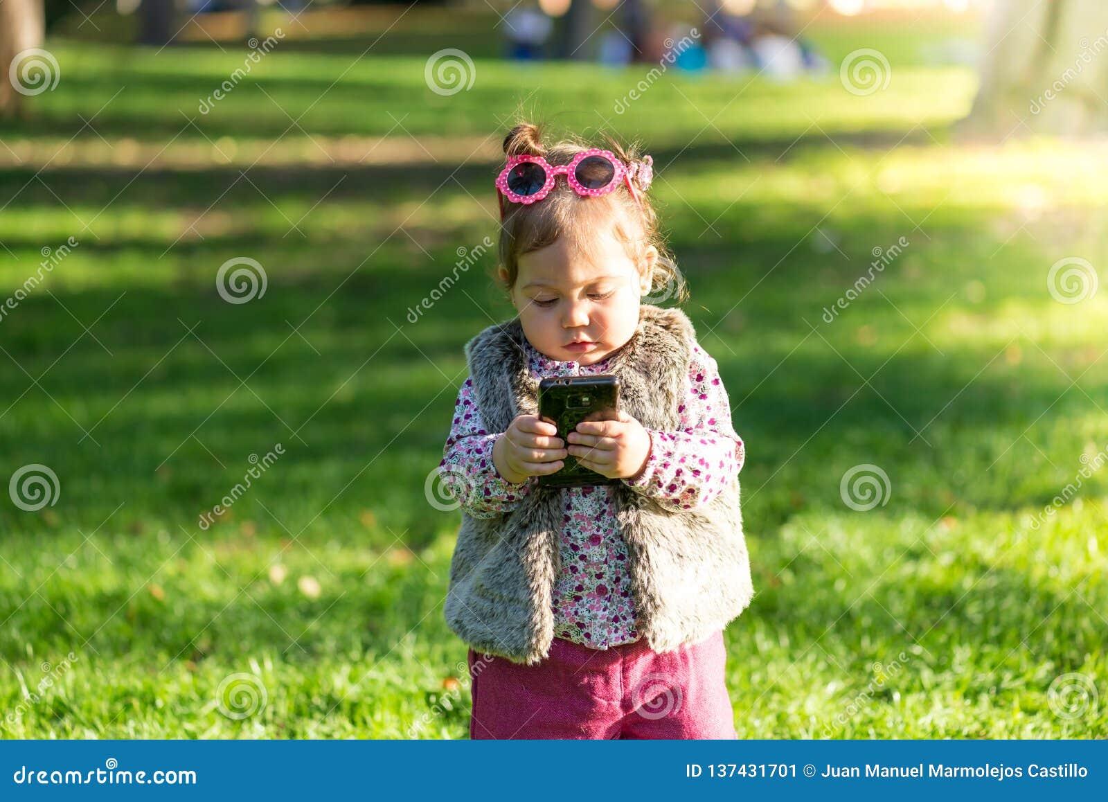 Piękna małe dziecko dziewczyna używa telefon komórkowego outdoors
