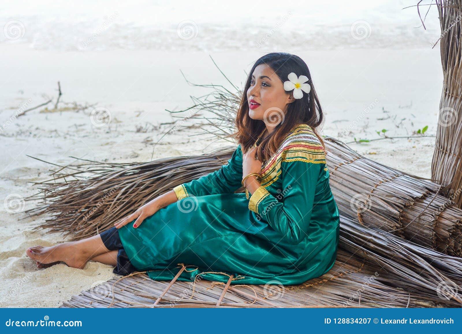 Piękna maldivian kobieta w obywatel sukni obsiadaniu na prześcieradłach robić od suchych liści