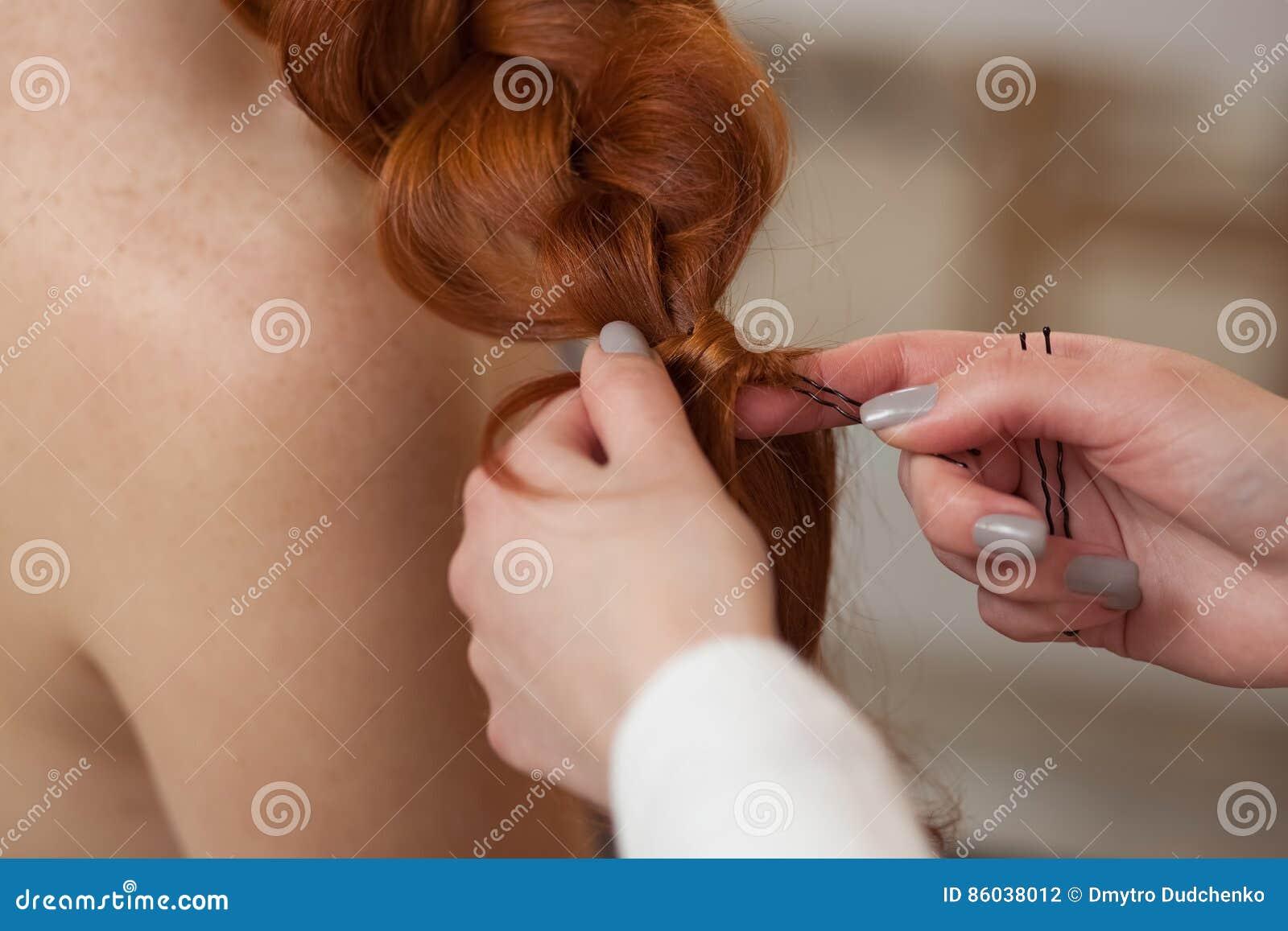 Piękna, miedzianowłosa dziewczyna z długie włosy, fryzjer wyplata Francuskiego warkocz w piękno salonie,