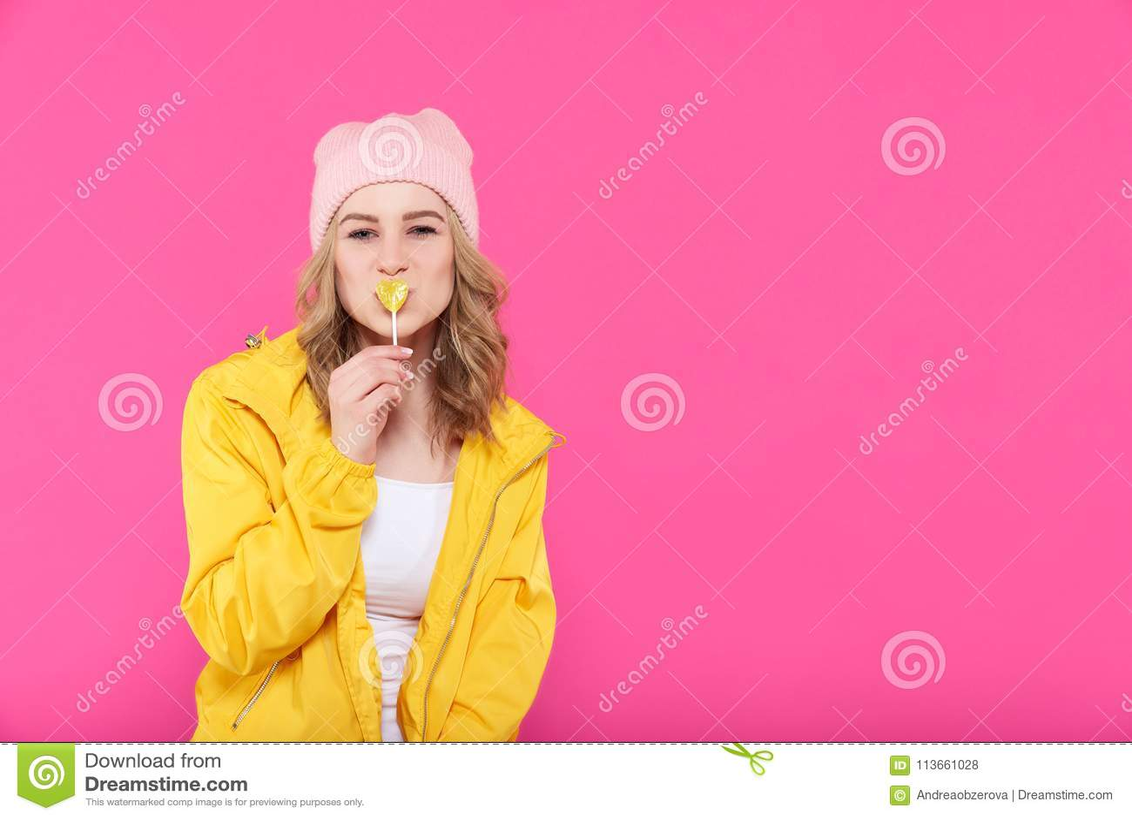 Piękna modna dziewczyna w kolorowych ubraniach i różowa beanie całowania sztuka kształtowaliśmy popsicle [on] Co] ol y] oung kobi
