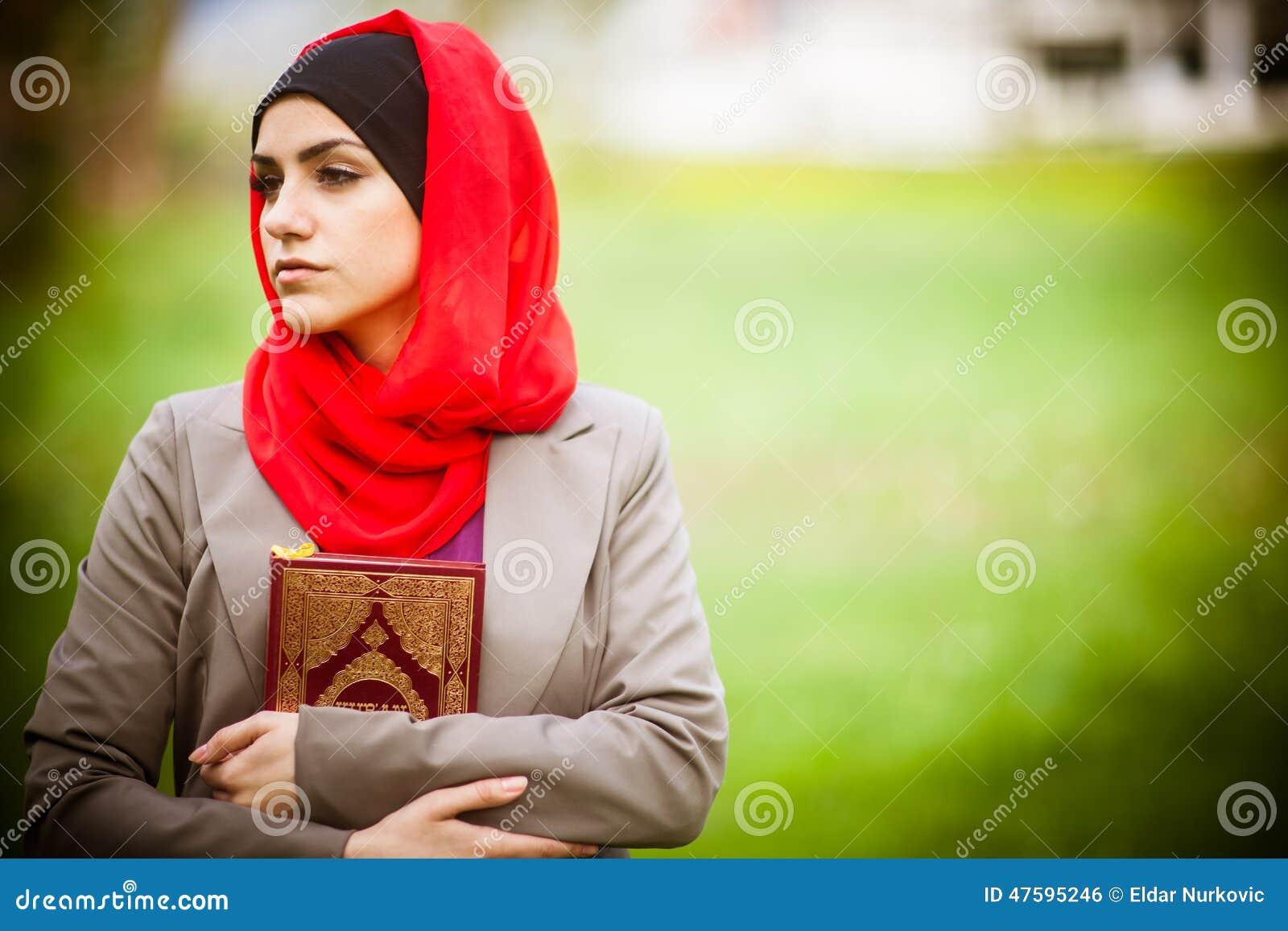 Piękna muzułmańska kobieta jest ubranym hijab i trzyma świętą księgę Koraniczna