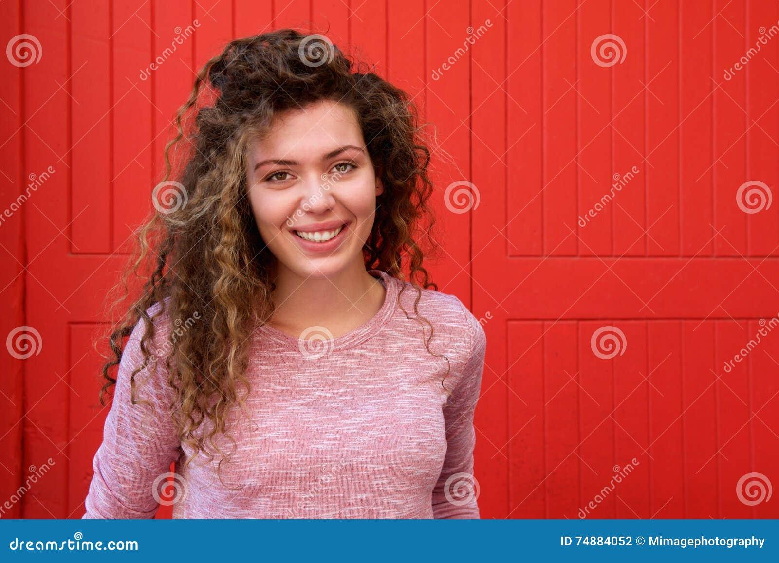 Piękna nastoletnia dziewczyna ono uśmiecha się przeciw czerwieni ścianie