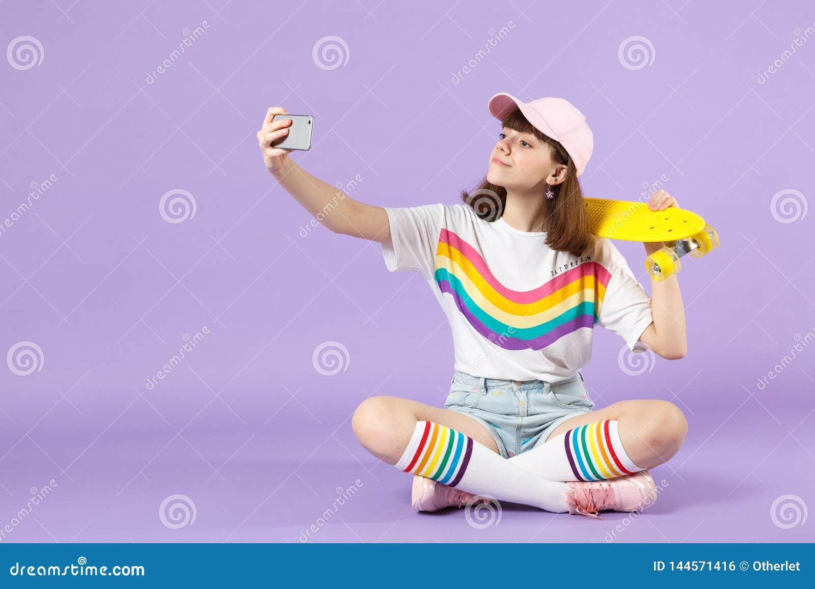 Piękna nastoletnia dziewczyna w żywego odzieżowego mienia żółty deskorolka, robi selfie strzelającemu na telefonie komórkowym odi