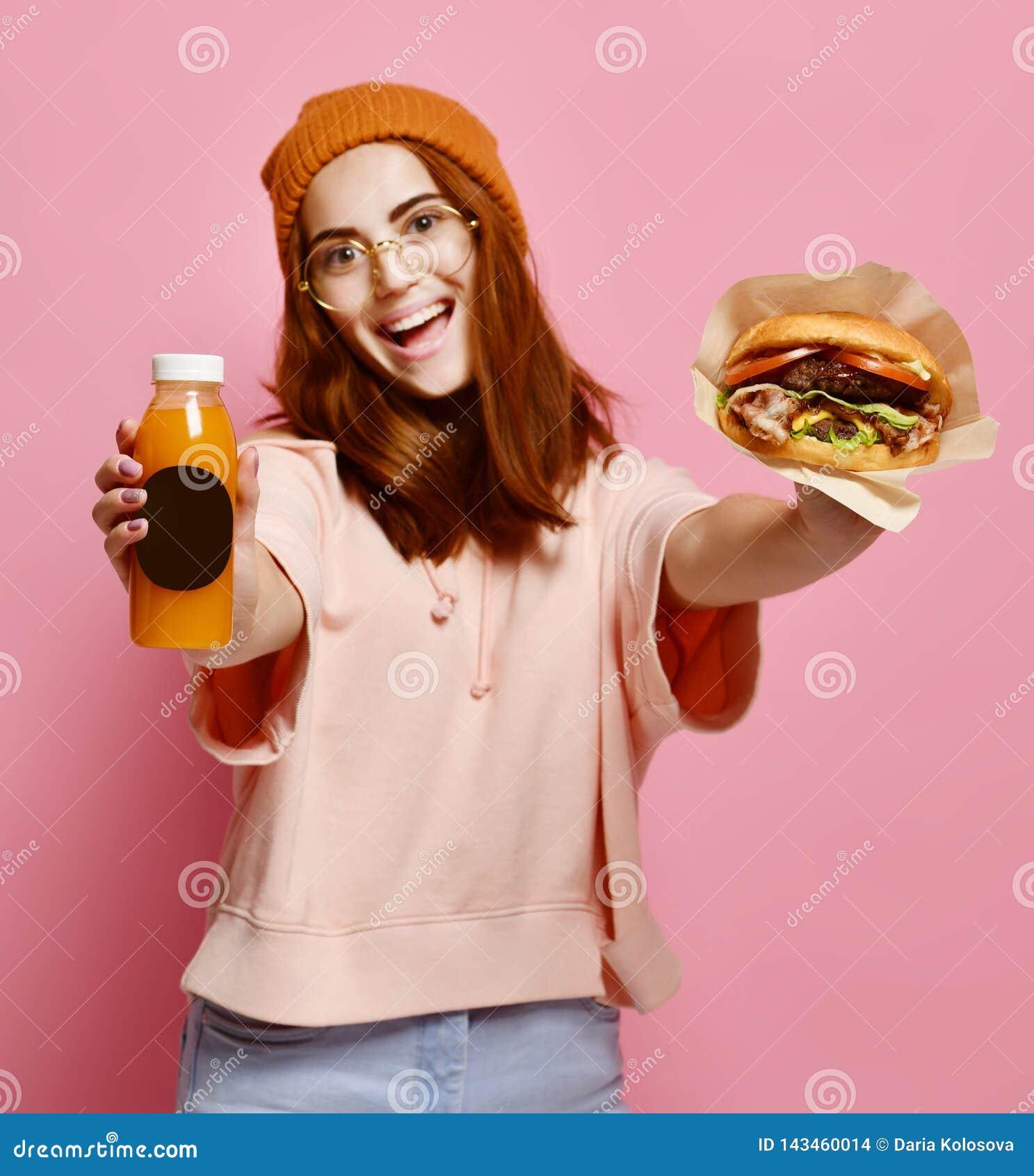 Piękna nastoletnia dziewczyna z czerwonym mienie hamburgerem, napojem w oba rękach włosy i kapeluszu i