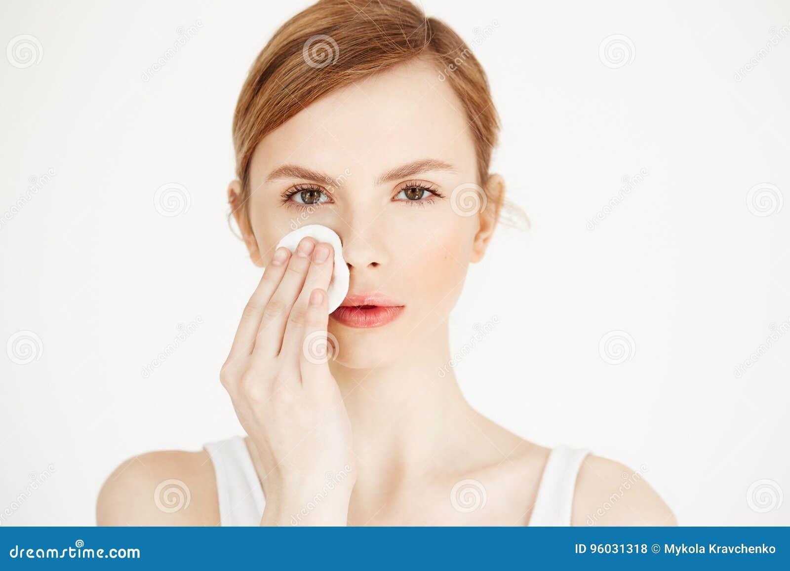 Piękna naturalna blondynki dziewczyny cleaning twarz z bawełnianą gąbką patrzeje kamerę nad białym tłem Kosmetologia i