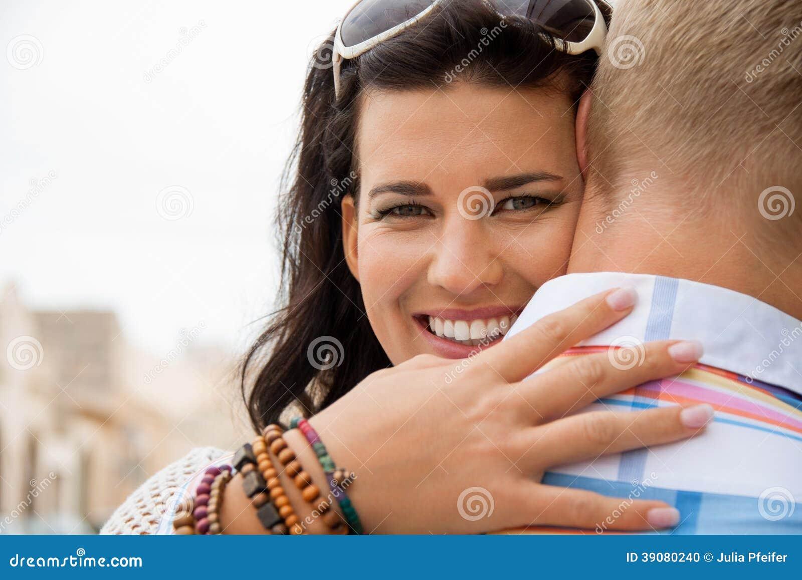 Piękna opromieniona kobieta ściska jej chłopaka