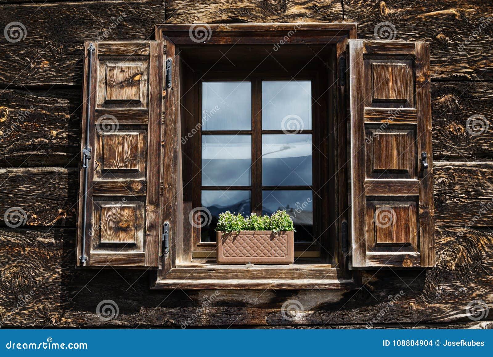 Piękna otwarta drewniana nadokienna żaluzja z kwiatami odbija niebieskie niebo