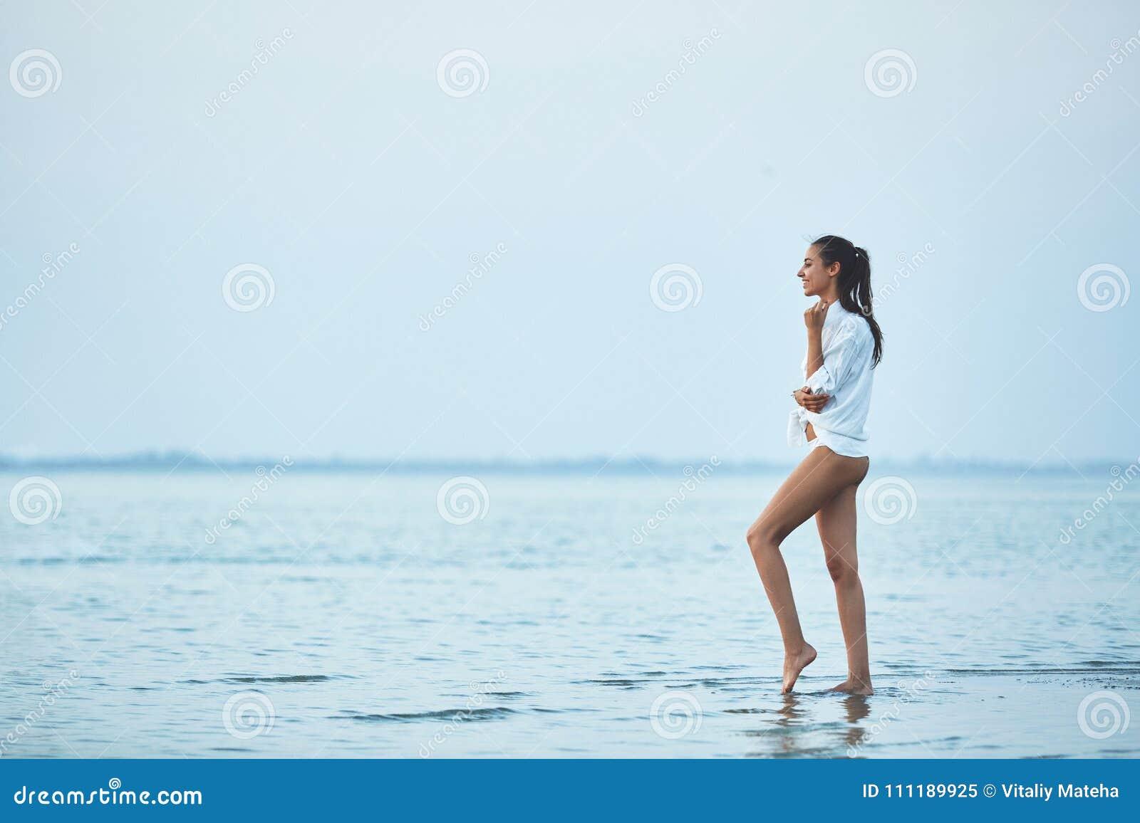 Piękna plciowa kobieta w białym koszula, bikini odprowadzeniu na plaży przeciw i