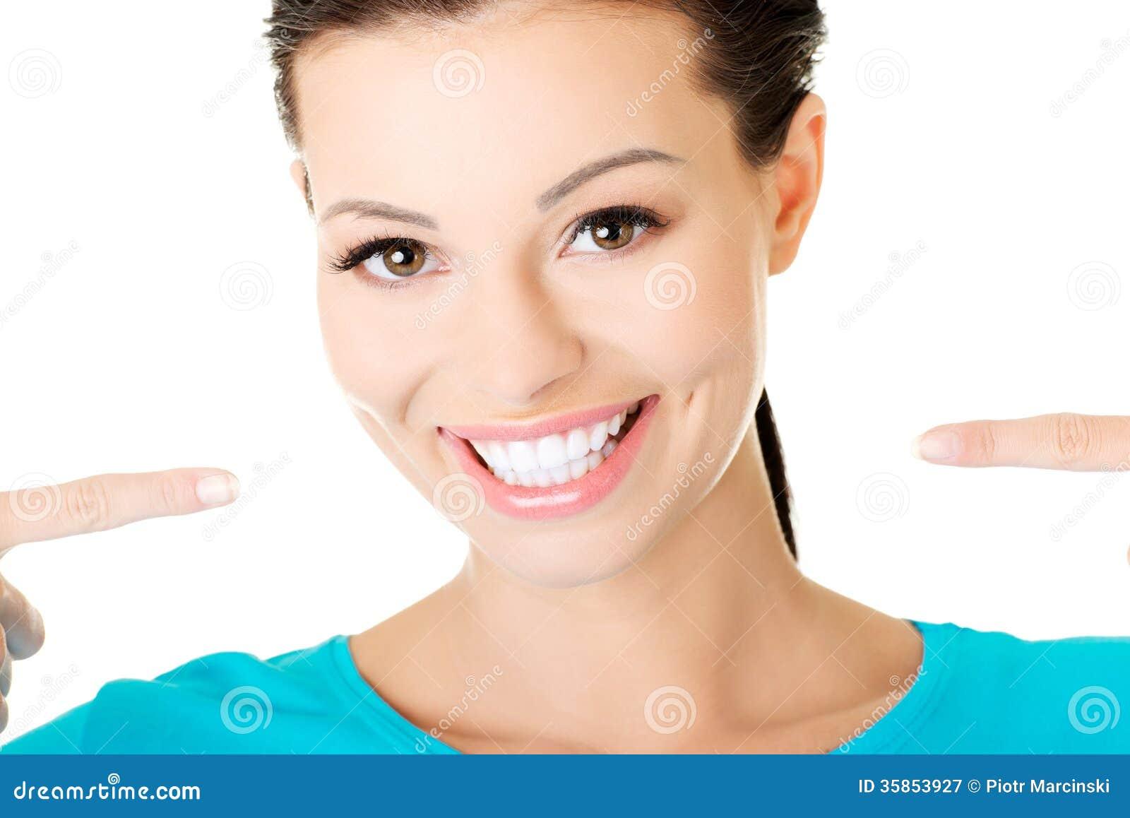 Piękna przypadkowa kobieta pokazuje ona perfect białych zęby.