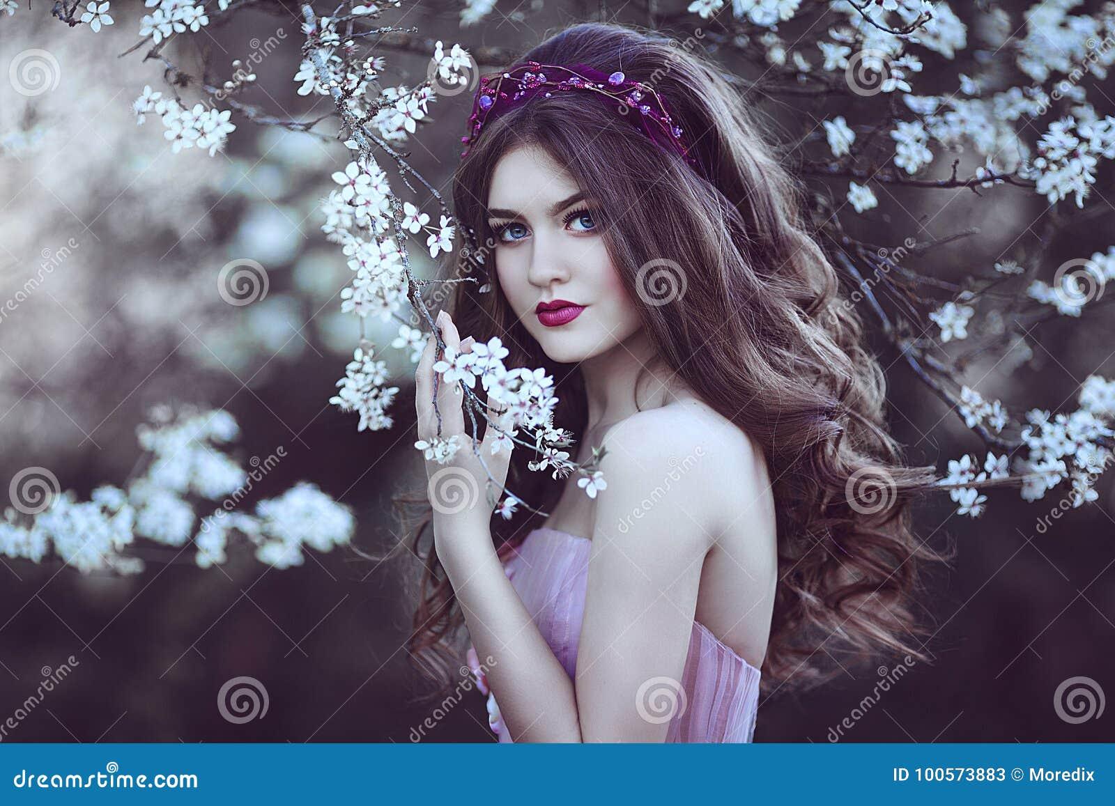 Piękna Romantyczna dziewczyna z długie włosy w menchii sukni blisko kwiatonośnego drzewa