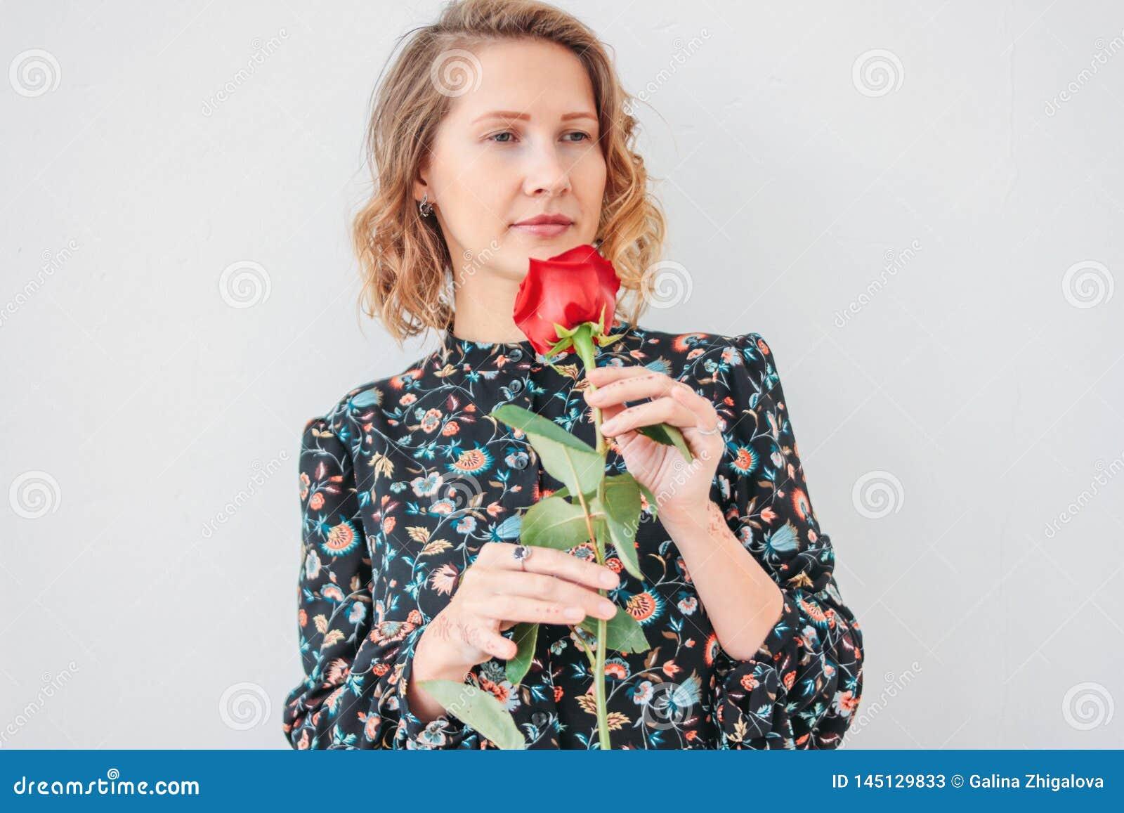Piękna romantyczna młoda blondynki kobieta w sukni z czerwieni różą na białym tle odizolowywającym