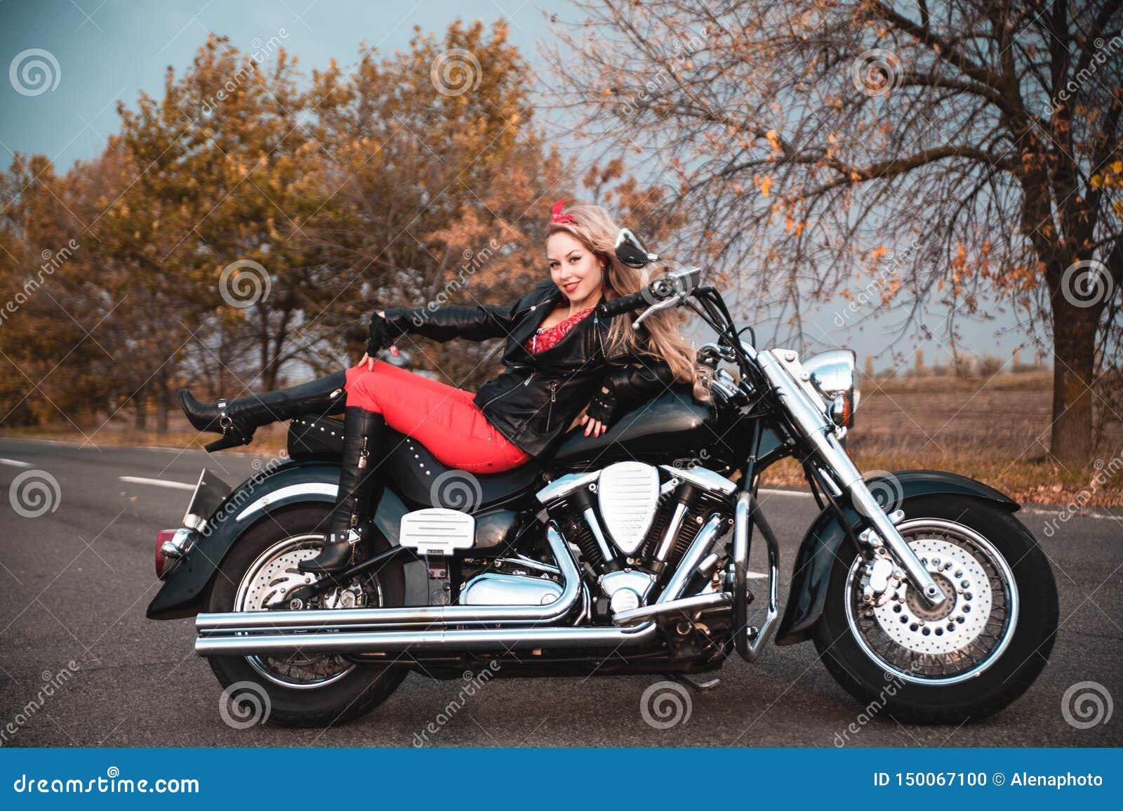 Piękna rowerzysta kobieta pozuje z motocyklem outdoors