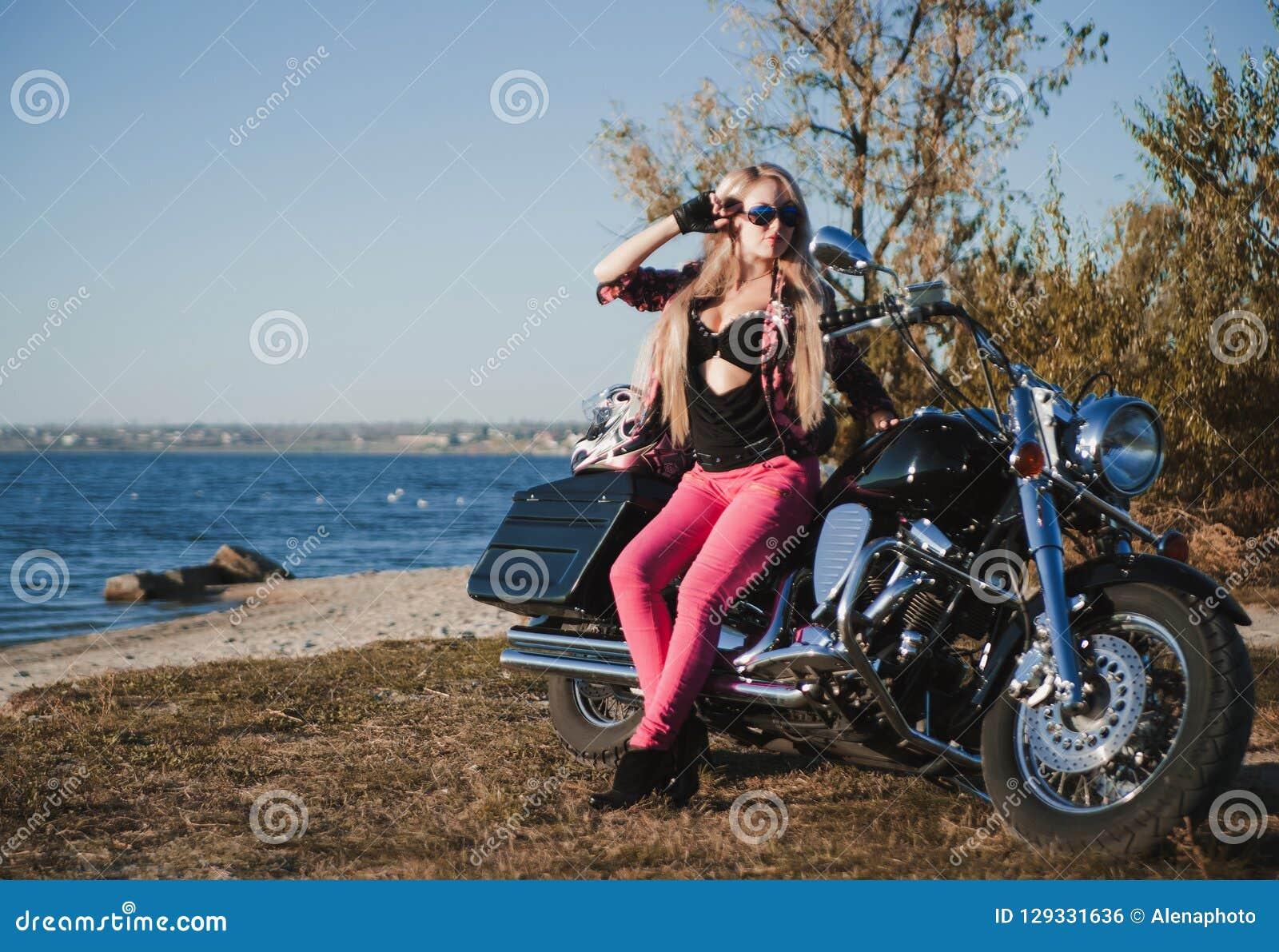 Piękna rowerzysta kobieta z motocyklem na plaży