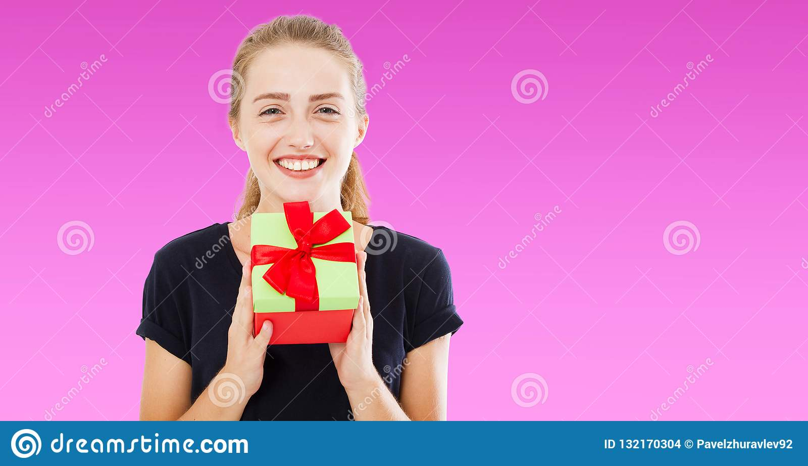 Piękna rozochocona kobieta w czarnej t koszula daje ci teraźniejszemu pudełku nad purpurowym tłem, wakacje pojęcie, kopii przestr