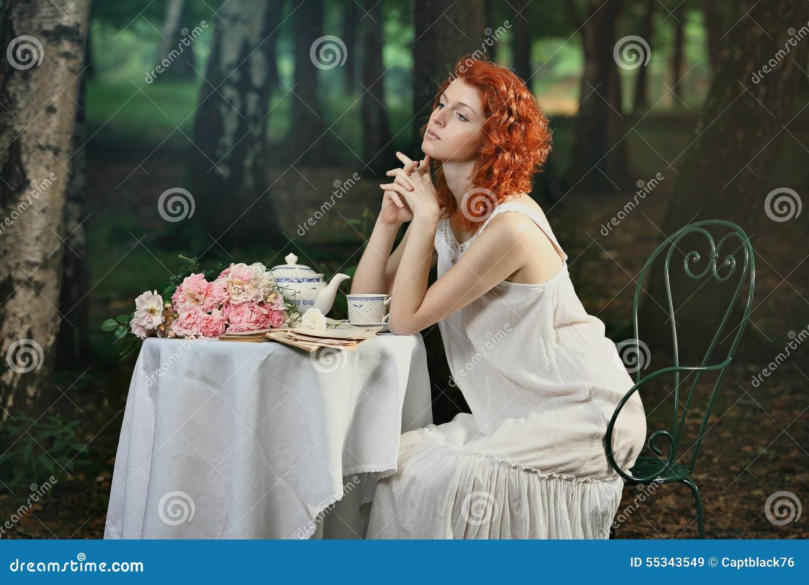 Piękna rudzielec kobieta ma herbaty w lesie