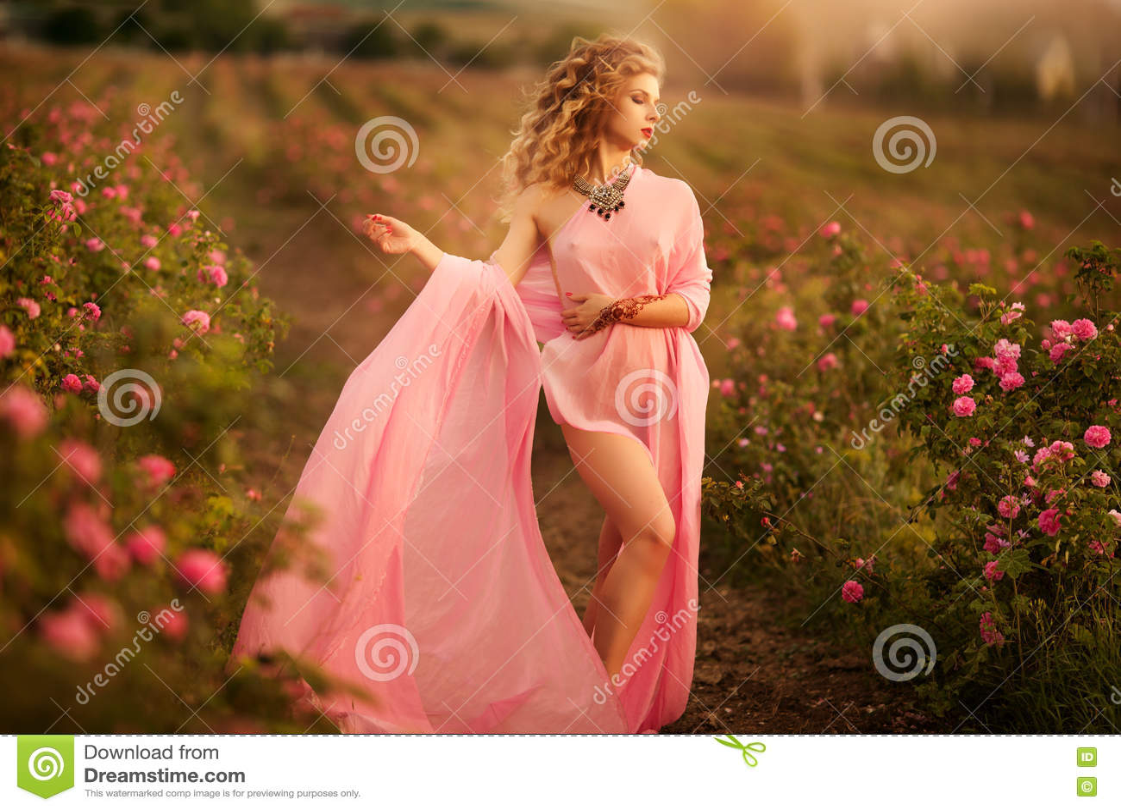 Piękna seksowna dziewczyna w różowej smokingowej pozyci w ogrodowych różach
