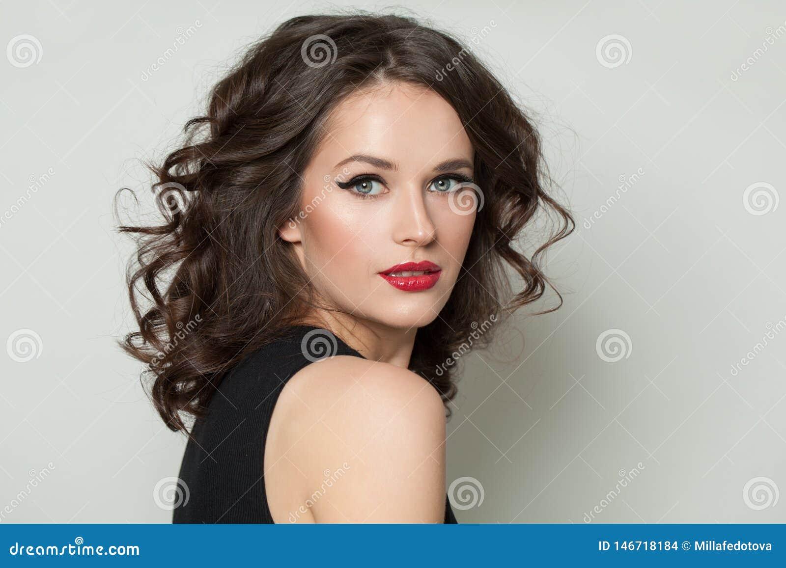 Piękna seksowna kobieta patrzeje kamerę Ładny model z makeup i brązu kędzierzawego włosy portretem