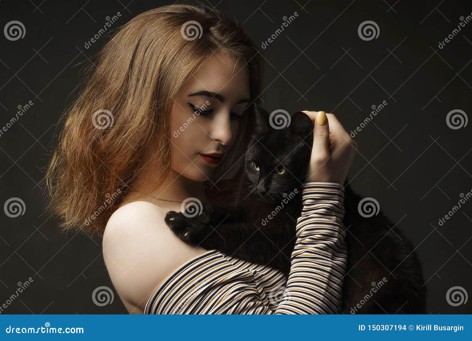 Piękna seksowna kobieta w czarnego mienia czarnym kocie Piękni potomstwa i elegancka kobieta trzyma szarego kota Pracowniana foto