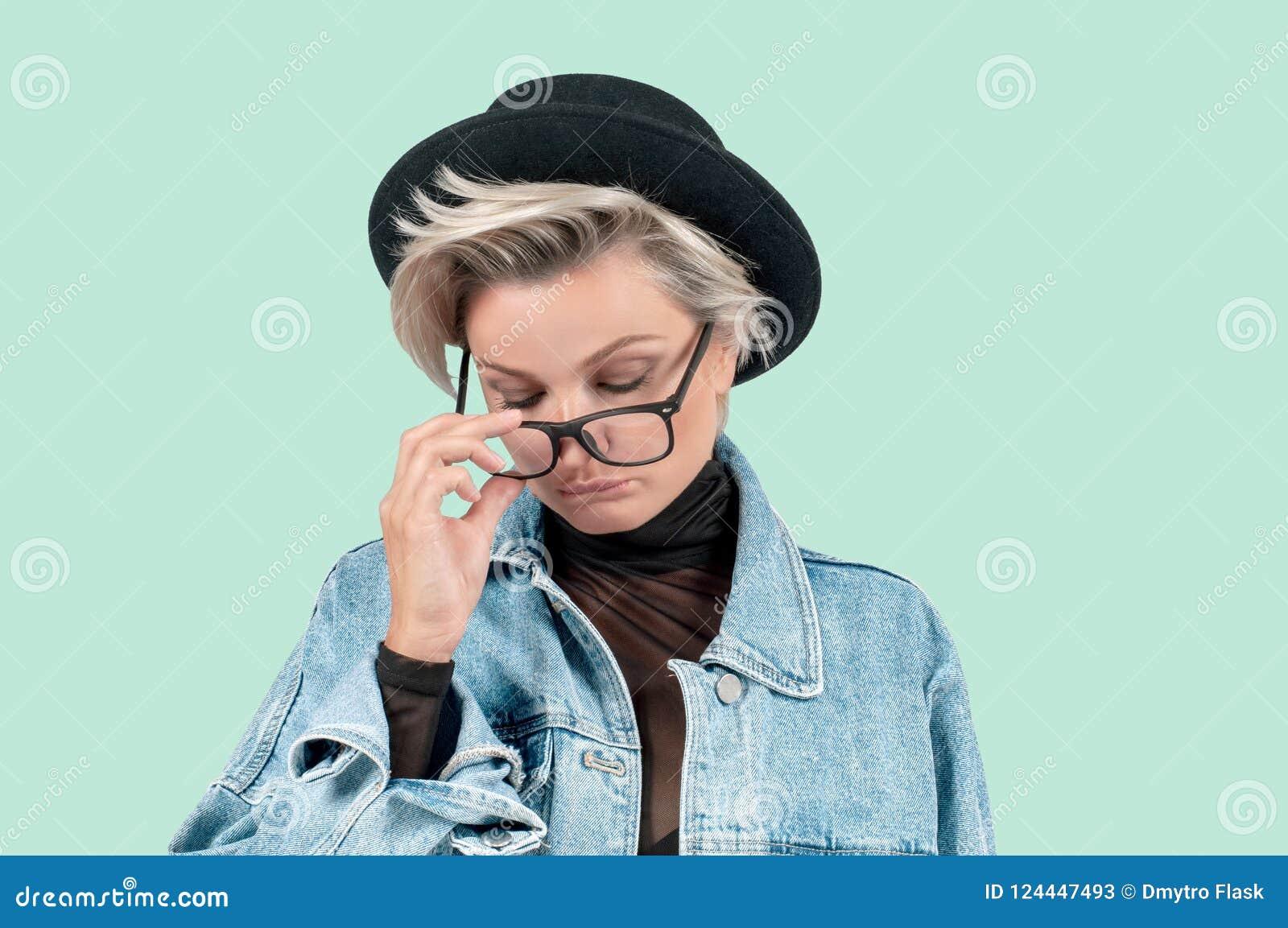 Piękna smutna kobieta z poważnym wyrazu twarzy uczuciem na zielonym tle