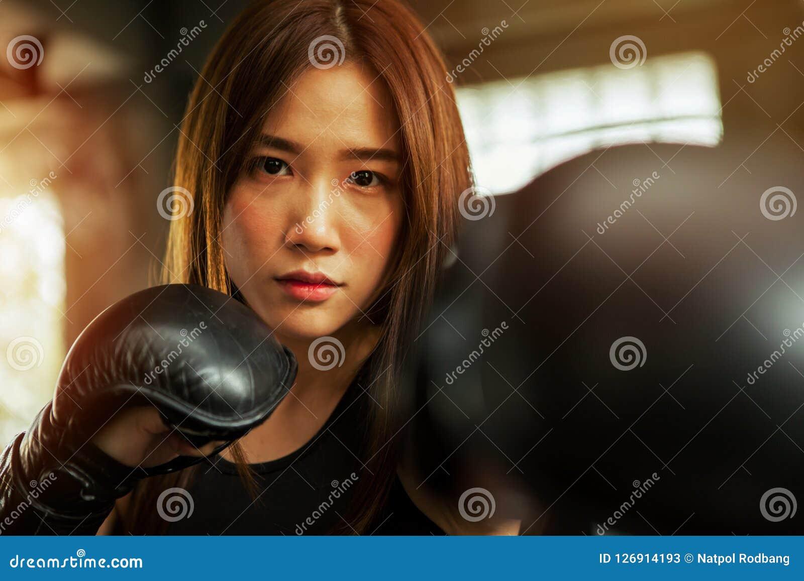 Piękna sportowa Azjatycka bokser kobieta uderza pięścią torbę z Boksować G