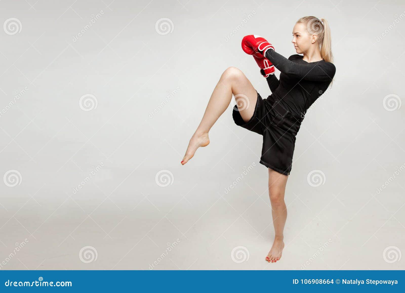 Piękna sportowa dziewczyna z bokserskimi rękawiczkami uderza wysoką stopę