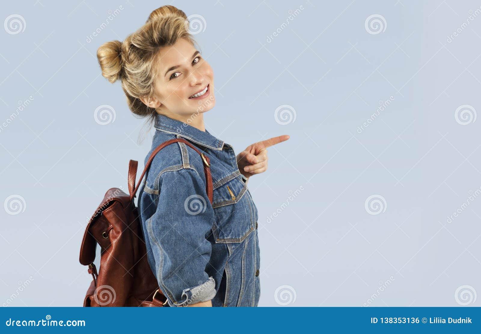 Piękna studencka dziewczyna w drelichowej kurtce z plecakiem na ona ramiona w studiu na błękitnym tle Pojęcie