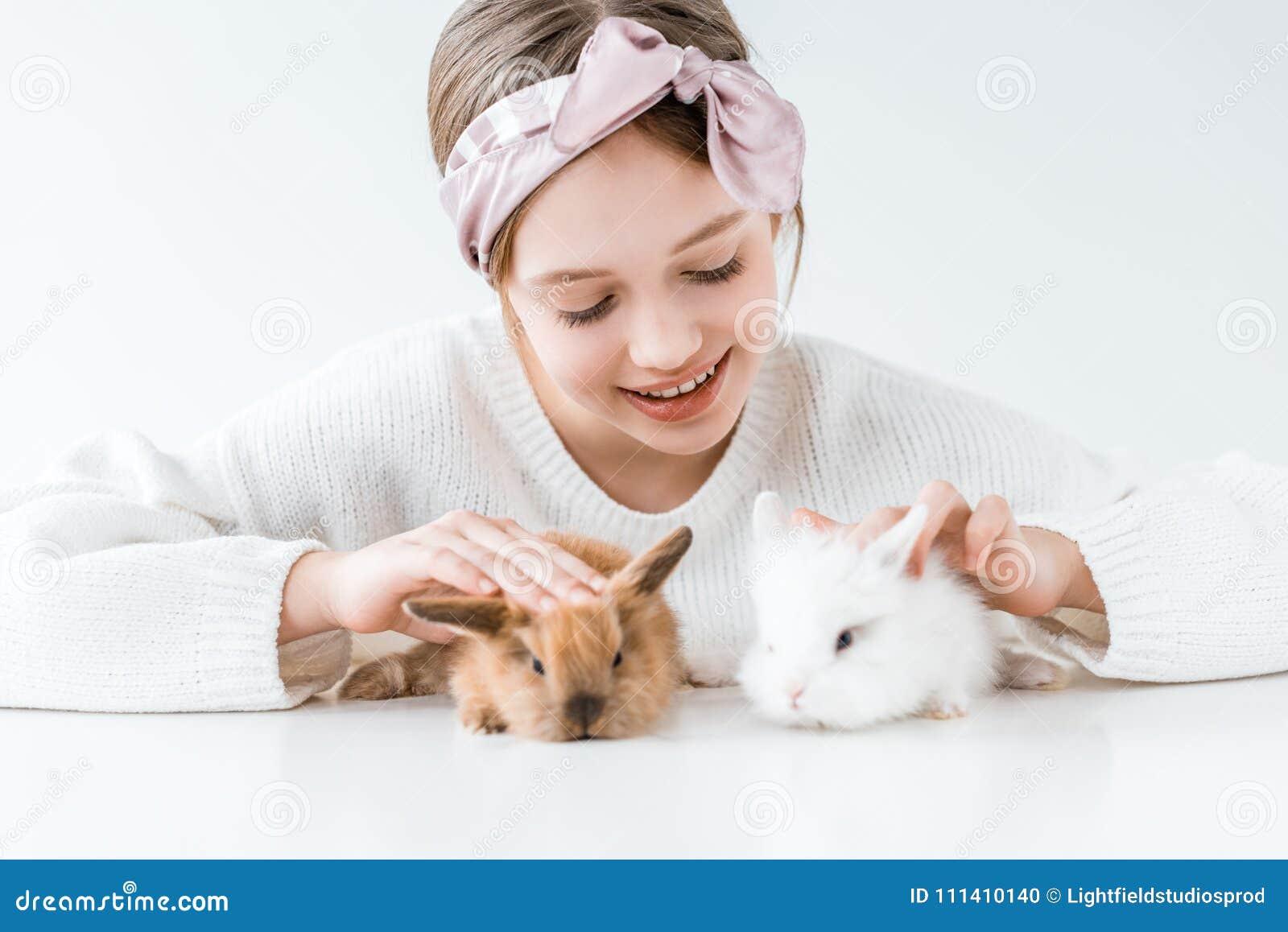Piękna szczęśliwa dziewczyna bawić się z uroczymi owłosionymi królikami