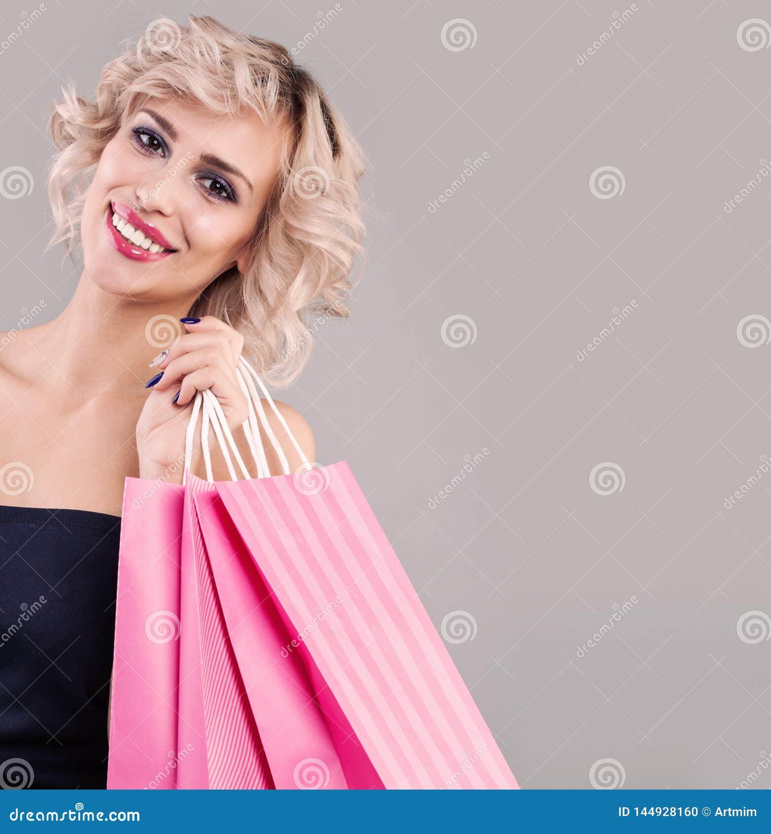 Piękna szczęśliwa kobiety mienia torba na zakupy Uśmiechnięta wzorcowa dziewczyna z makeup i ślicznym uśmiechem