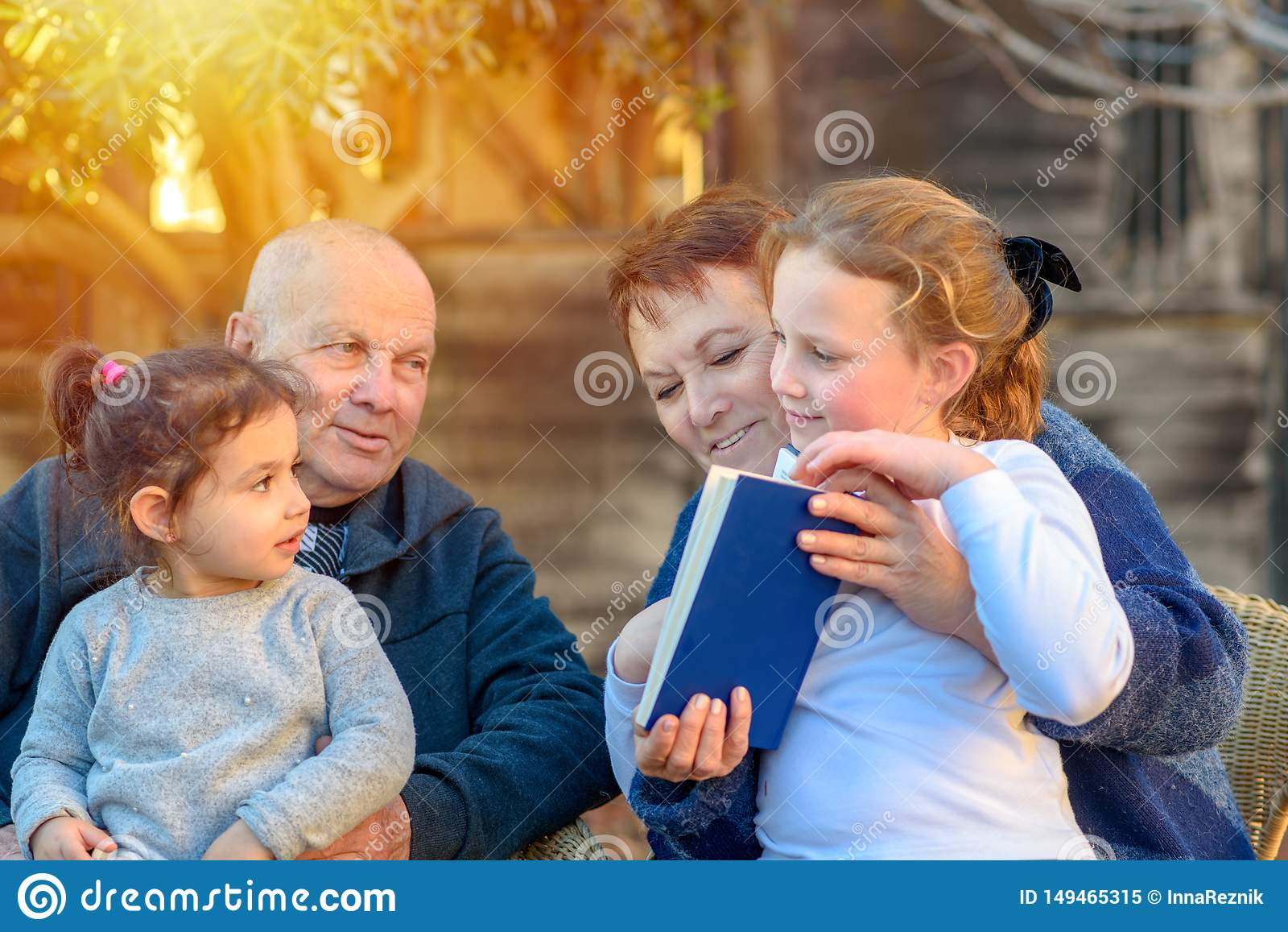 Piękna Szczęśliwa Stara para i wnuczki czyta książkę wpólnie w naturze przy zmierzchem