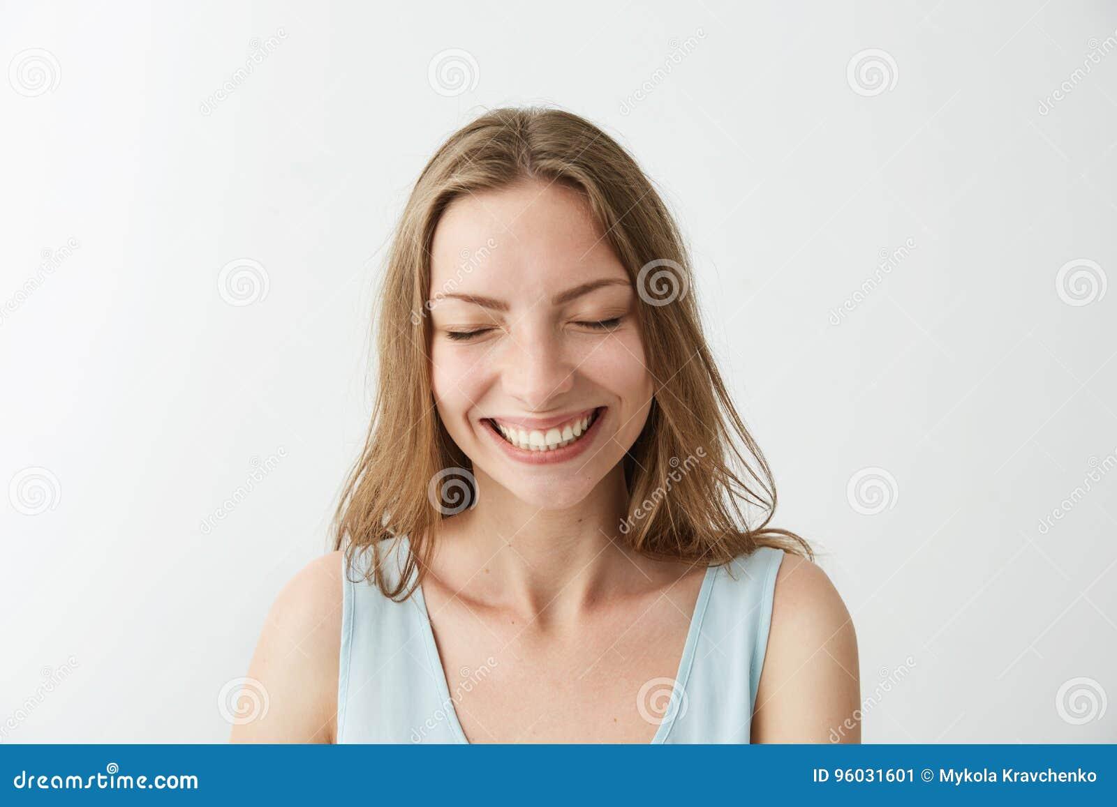 Piękna szczera szczęśliwa rozochocona dziewczyna uśmiecha się śmiać się z zamkniętymi oczami nad białym tłem