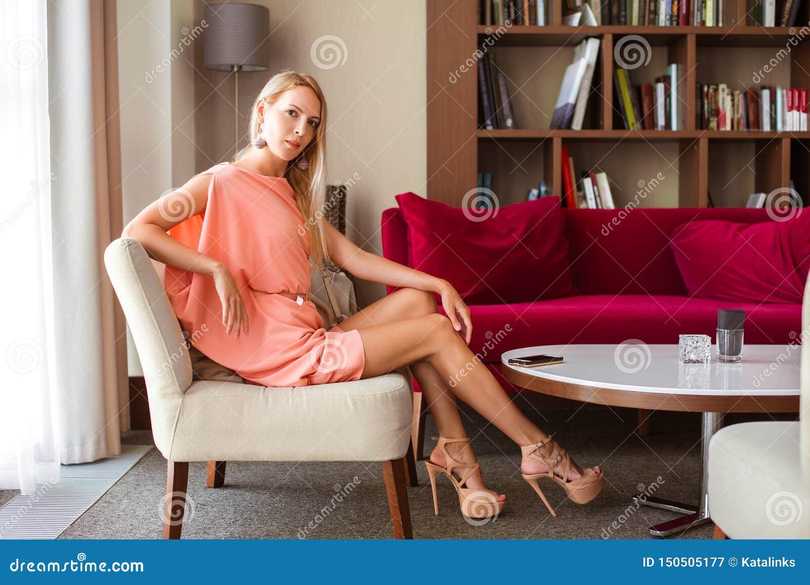 Piękna szczupła dziewczyny blondynka w modnej różowej lato sukni w szpilkach siedzi na krześle w pięknym żywym pokoju