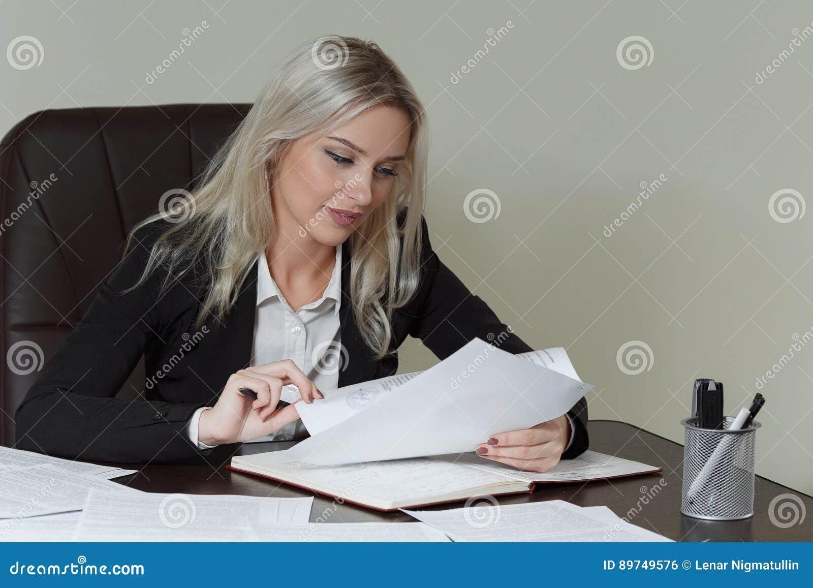 Piękna uśmiechnięta biznesowa kobieta pracuje przy jej biurowym biurkiem z dokumentami