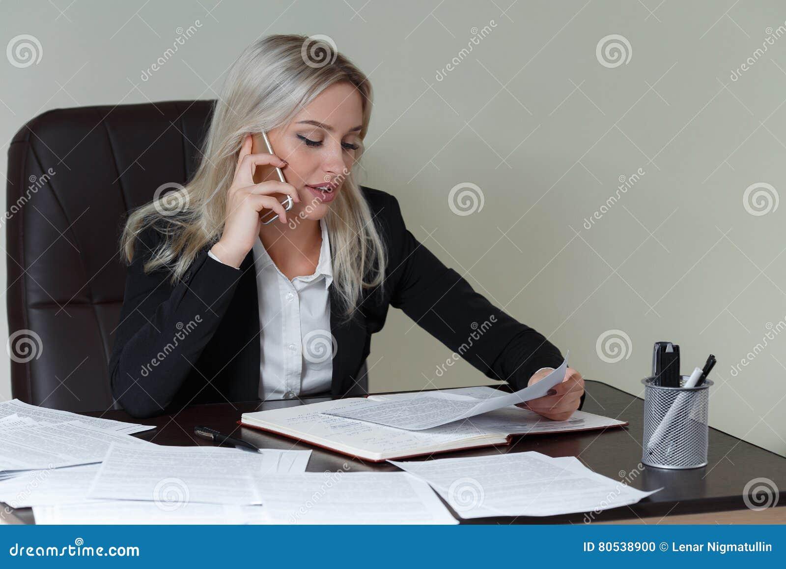 Piękna uśmiechnięta biznesowa kobieta pracuje przy jej biurowym biurkiem z dokumentami i opowiada na telefonie