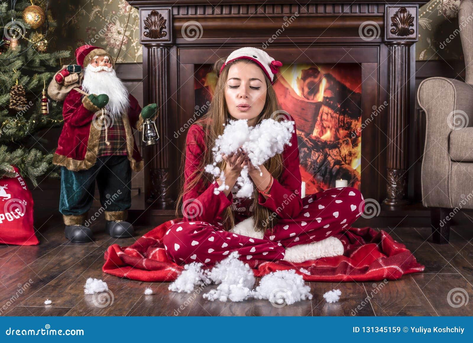Piękna uśmiechnięta dziewczyna w czerwonych bożych narodzeń domowych odzieżowych pyjamas siedzi pod choinką blisko graby i dmucha