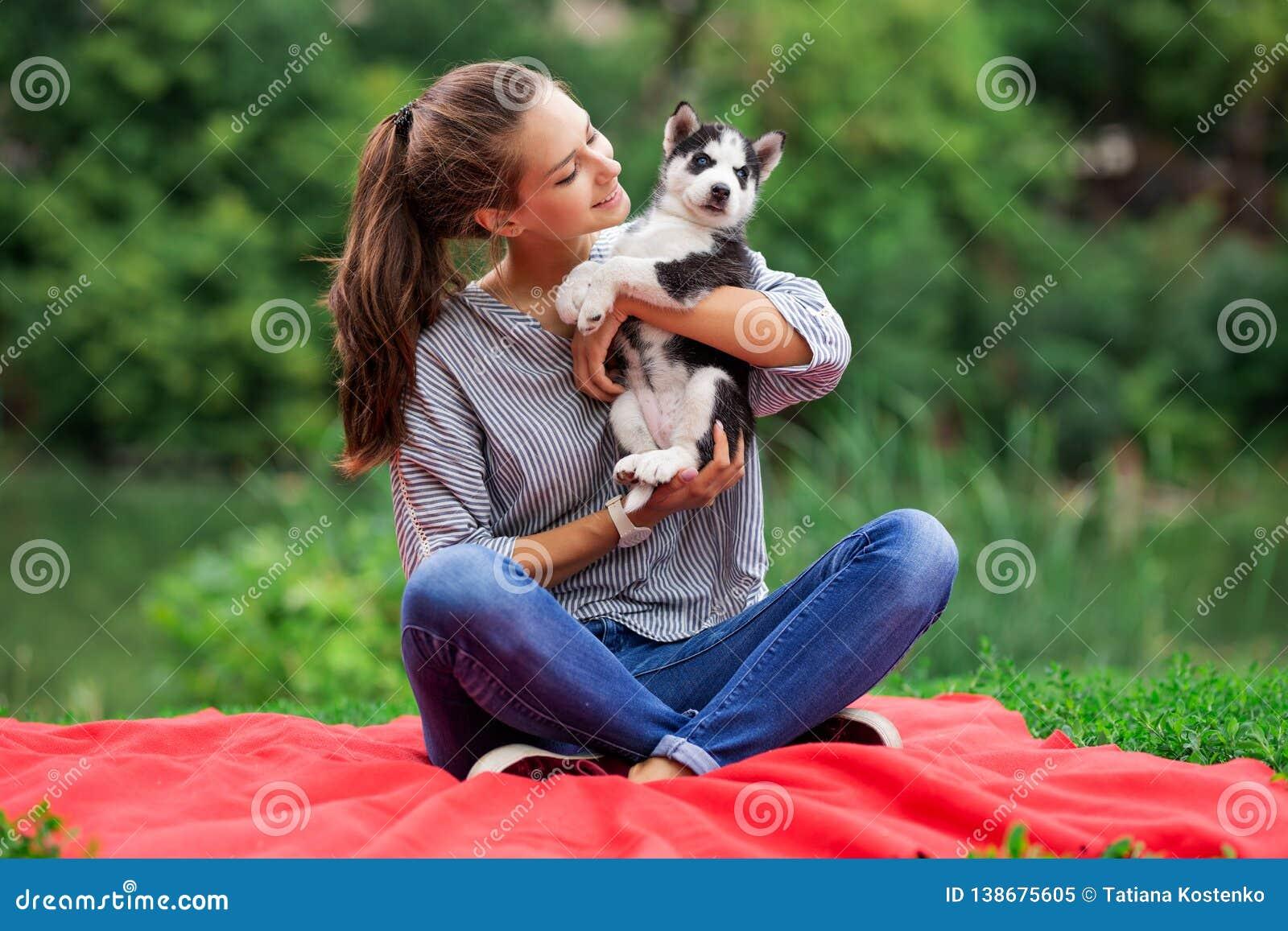 Piękna uśmiechnięta kobieta odpoczywająca z ponytail i być ubranym pasiastą koszula cuddling z słodkim łuskowatym szczeniakiem po