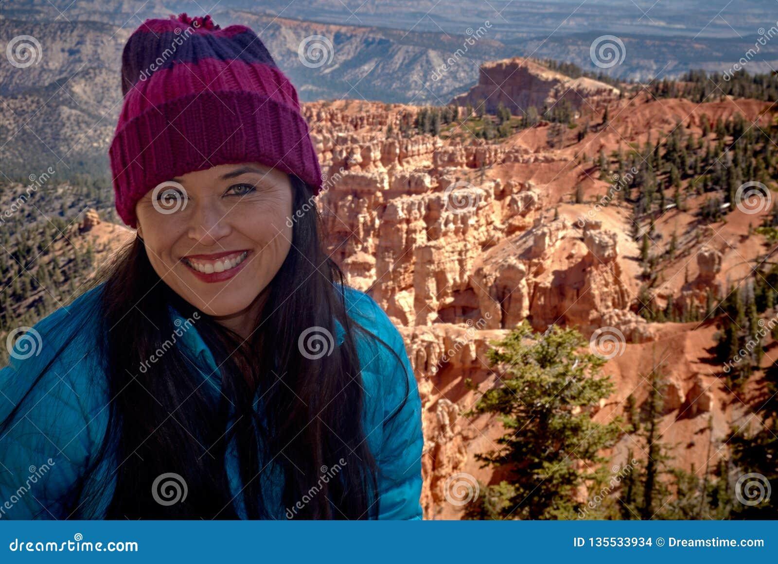 Piękna uśmiechnięta kobieta przy Bryka jarem w zimie z błękitnym żakietem i purpury dziamy kapelusz
