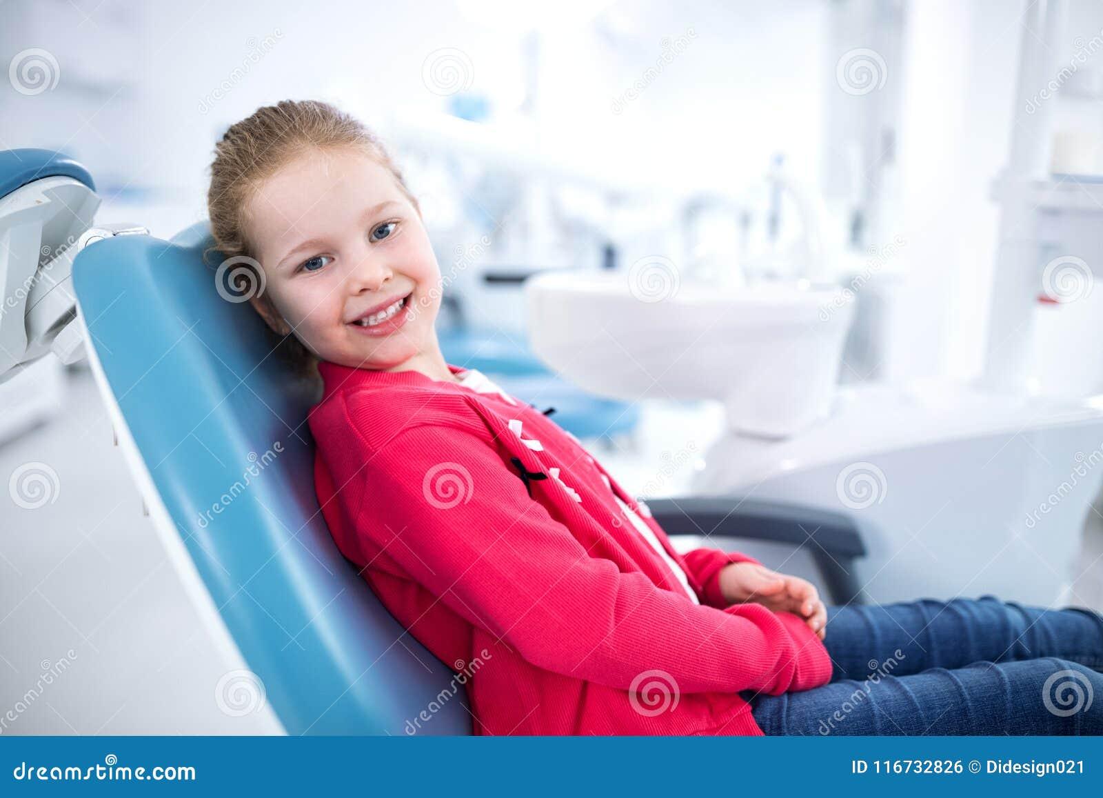 Piękna uśmiechnięta mała dziewczynka w stomatologicznym biurze