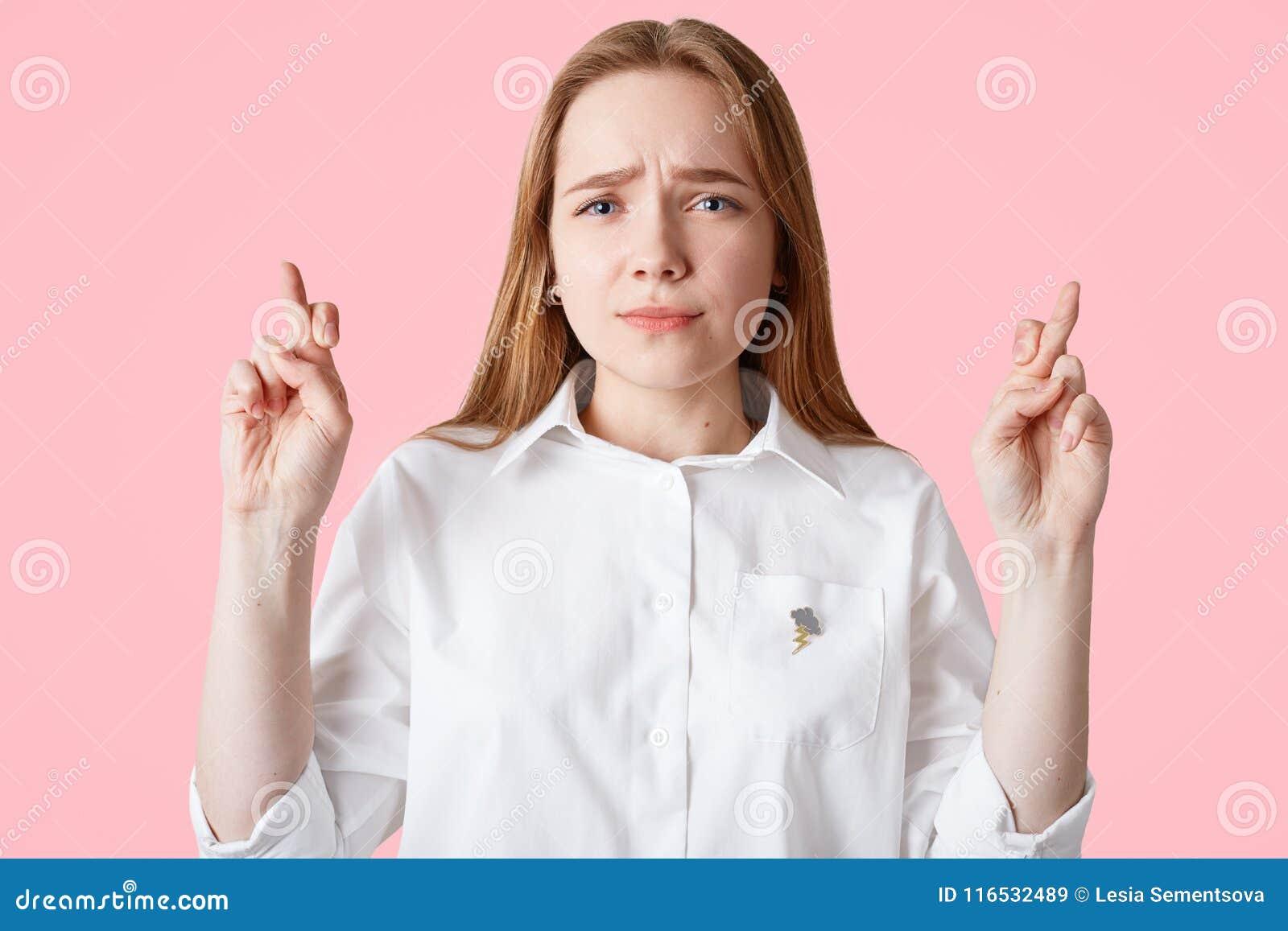 Piękna urocza Kaukaska kobieta utrzymuje palce krzyżuje, spojrzenia z dużą nadzieją przy kamerą, jest ubranym przypadkową bielu t