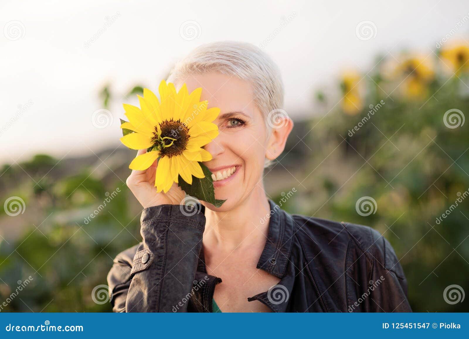 Piękna wiek średni kobieta outdoors stoi między słonecznikami w wiejskiej śródpolnej scenie