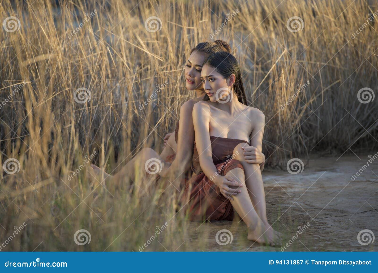 Piękne Azjatyckie kobiety siedzi w trawy polu jest ubranym Tajlandzką tradycję w wieczór