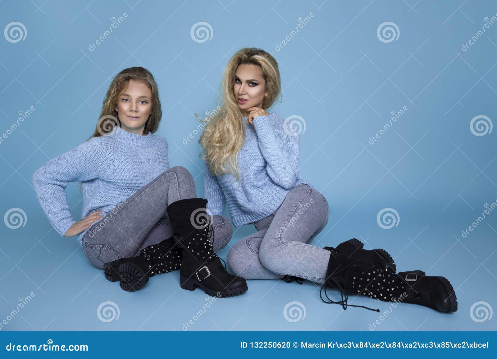 Piękne blond dziewczyny, matka z córką w jesieni zimy odzieży na błękitnym tle w studiu
