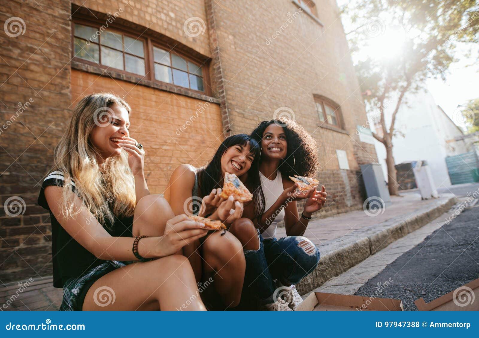 Piękne dziewczyny siedzi outdoors drogową łasowanie pizzą