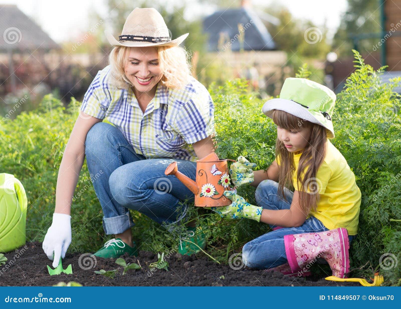 Piękne kobiety i chid córki flancowania rozsady w łóżku w domowym ogródzie przy letnim dniem Ogrodnictwo aktywność z