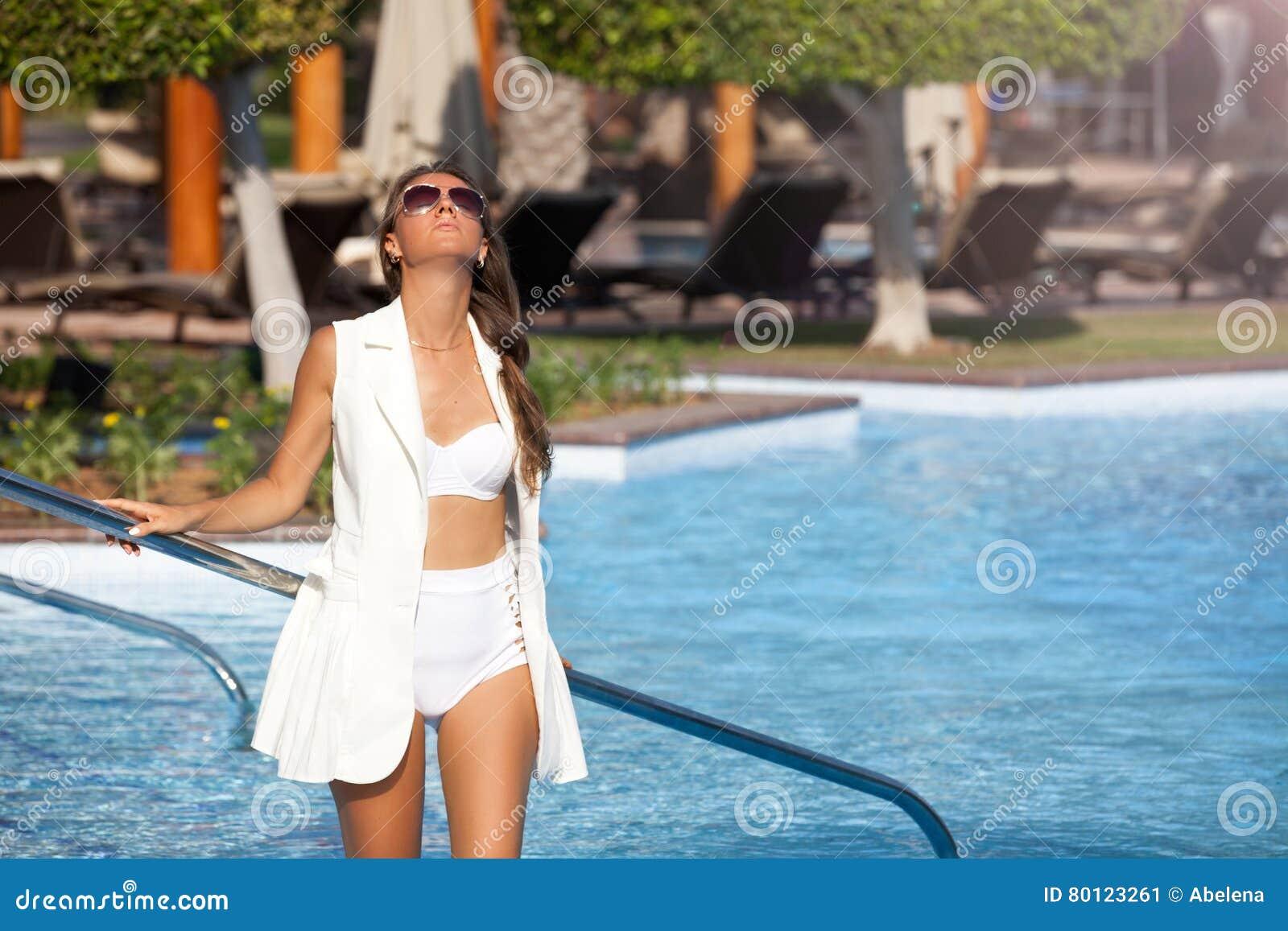 Piękne kobiety relaksuje blisko luksusowego poolside